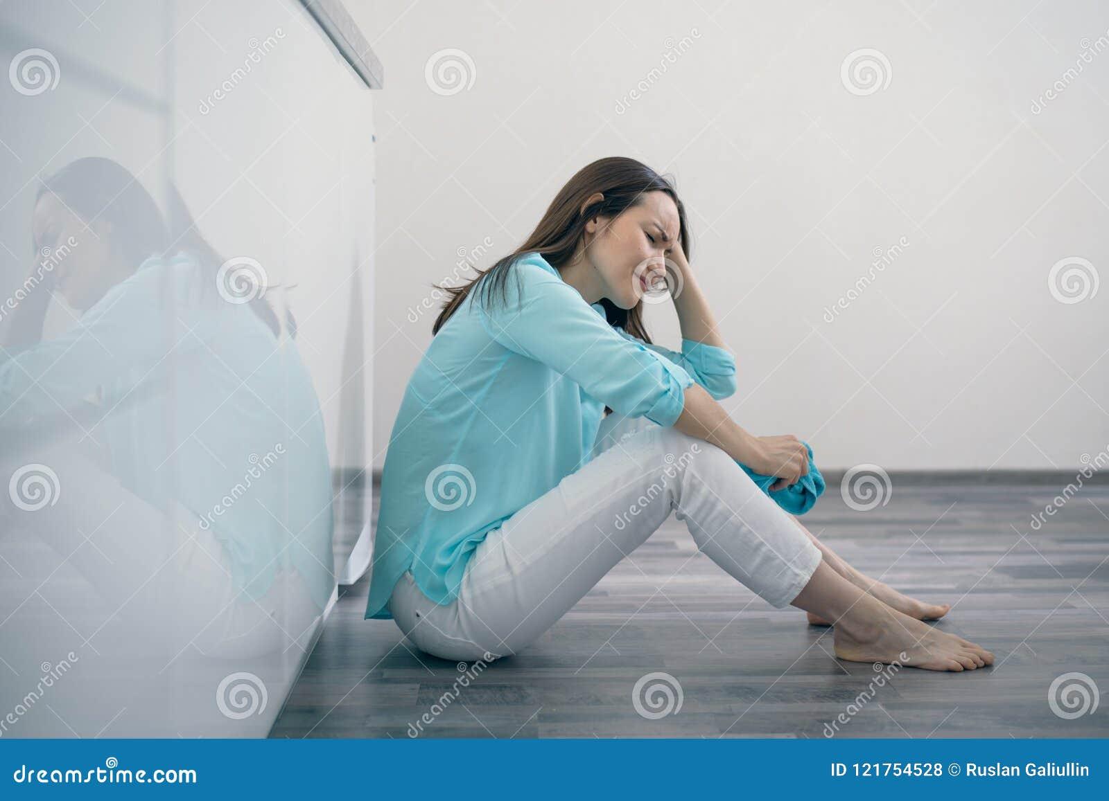 Νέα συνεδρίαση γυναικών στο πάτωμα κουζινών το κεφάλι και να φωνάξει της, που ανατρέπεται που κρατούν, λυπημένος, καταθλιπτικά