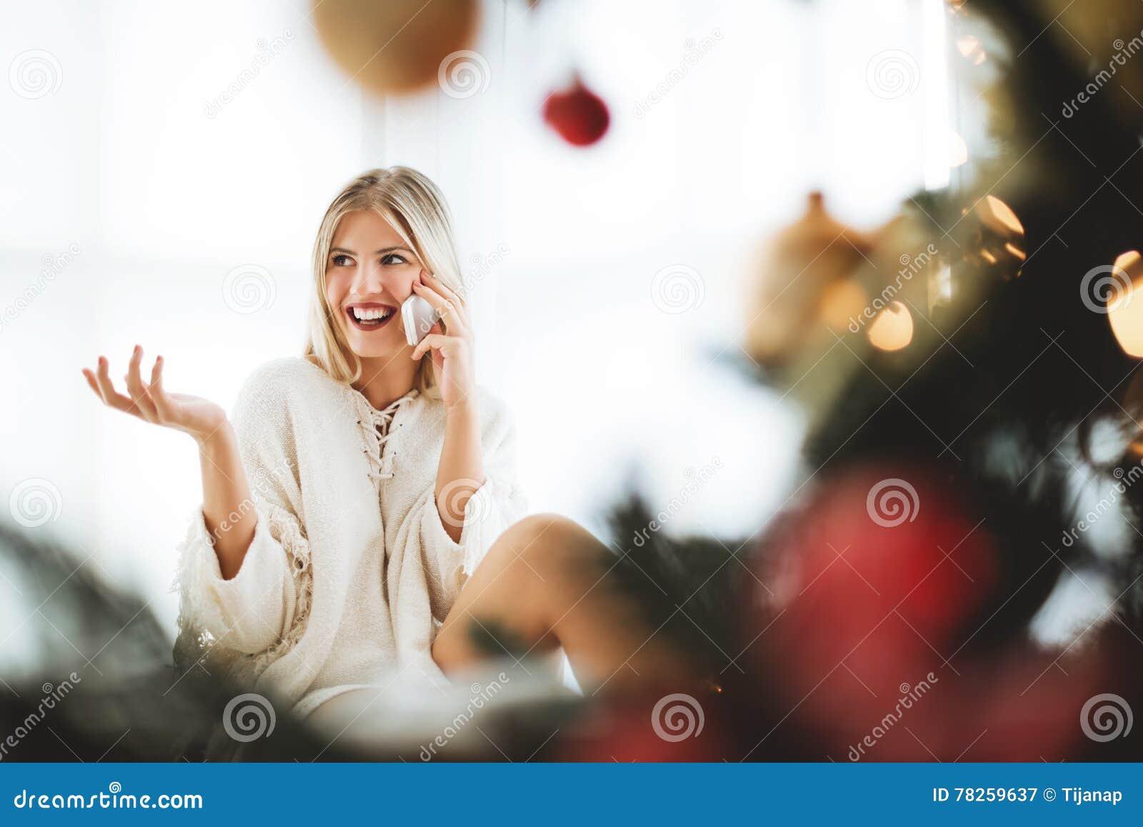 Νέα συνεδρίαση γυναικών δίπλα σε ένα χριστουγεννιάτικο δέντρο, που μιλά πέρα από το τηλέφωνο