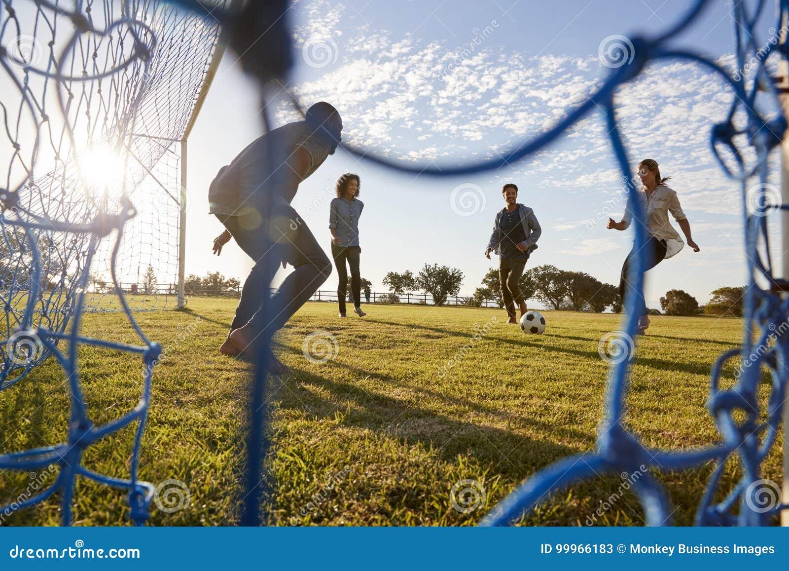 Νέα τρεξίματα γυναικών σε ένα ποδόσφαιρο παίζοντας με τους φίλους