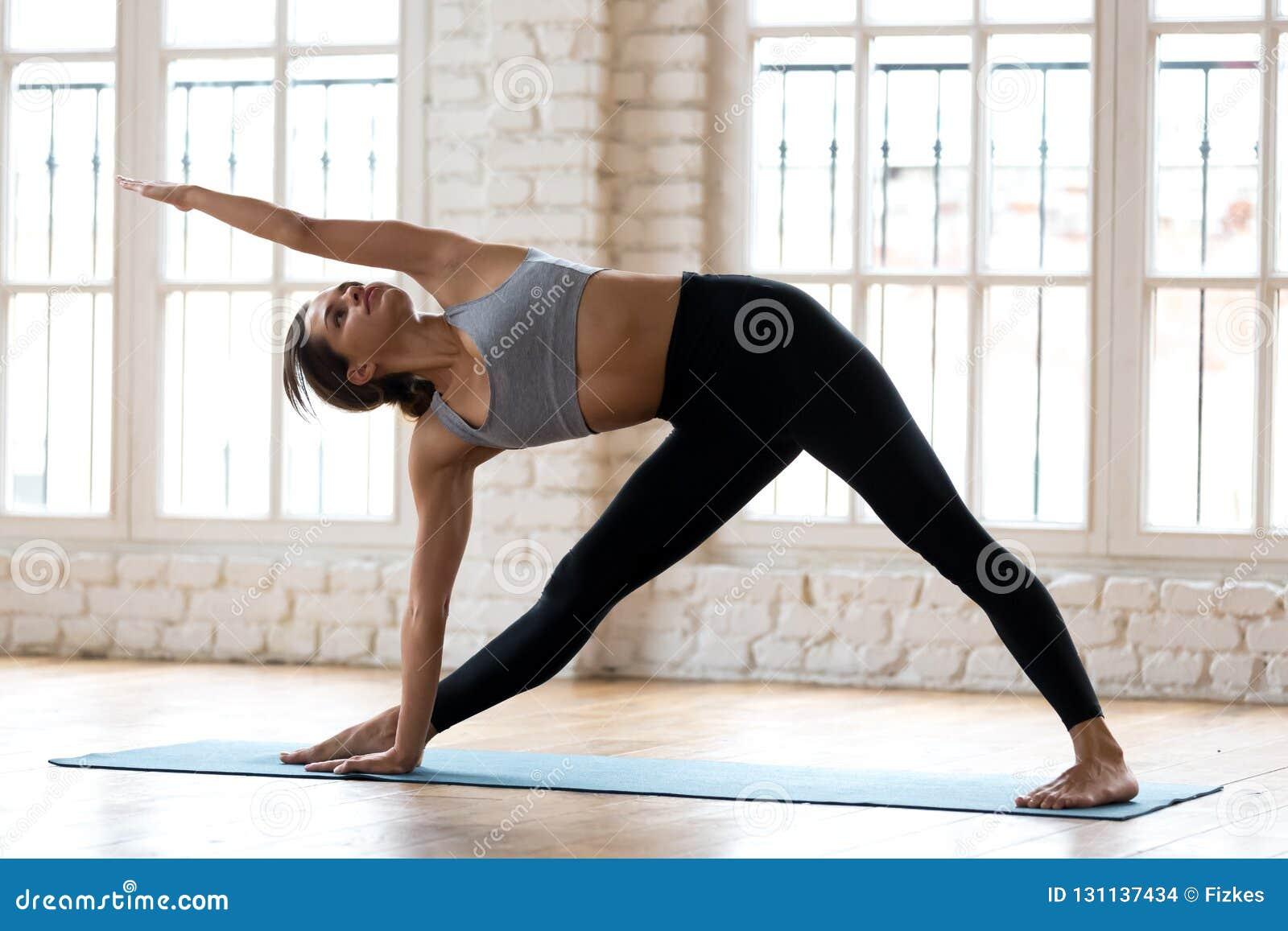 Νέα φίλαθλη ελκυστική γιόγκα άσκησης γυναικών, που κάνει Utthita τρι