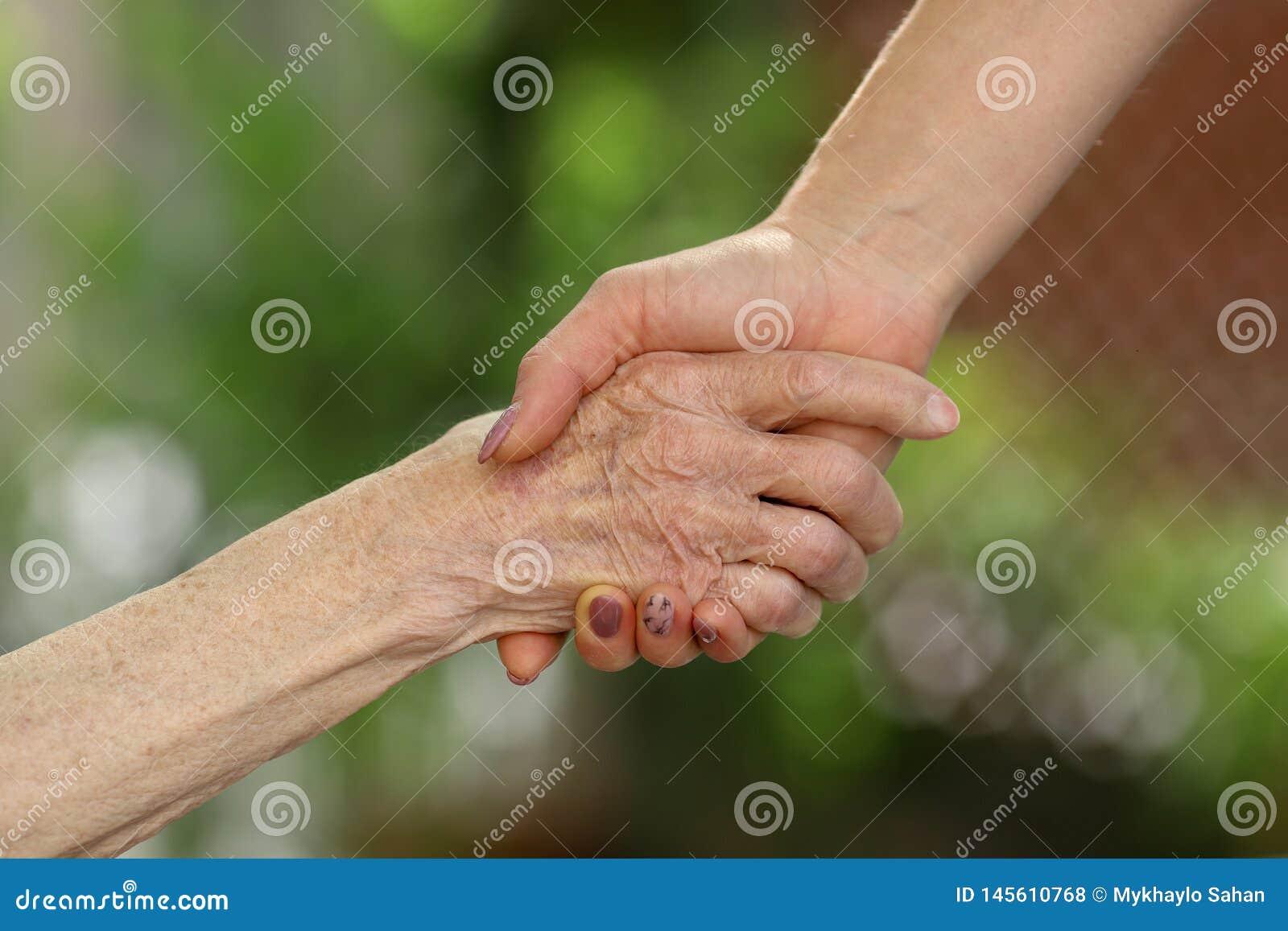 Νέα χέρια πρεσβυτέρων εκμετάλλευσης caregiver Χέρια βοηθείας, προσοχή για την ηλικιωμένη έννοια