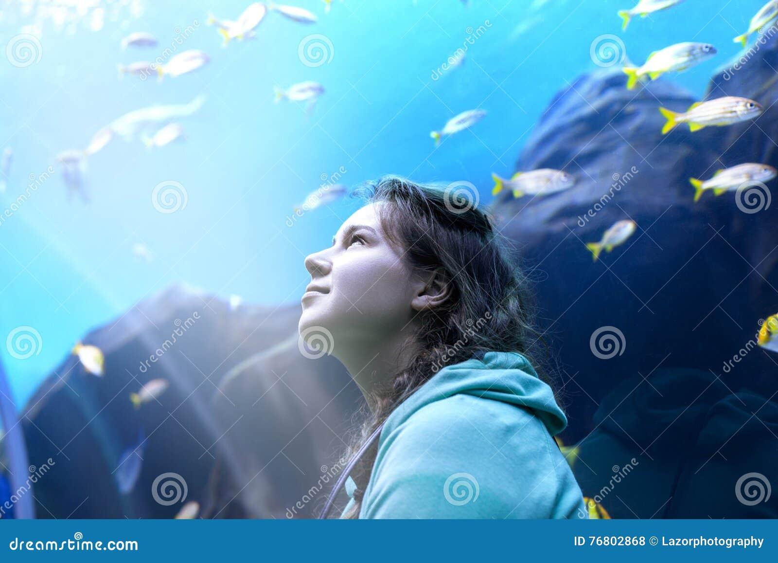 Νέα όμορφα ψάρια προσοχής γυναικών σε ένα τροπικό ενυδρείο