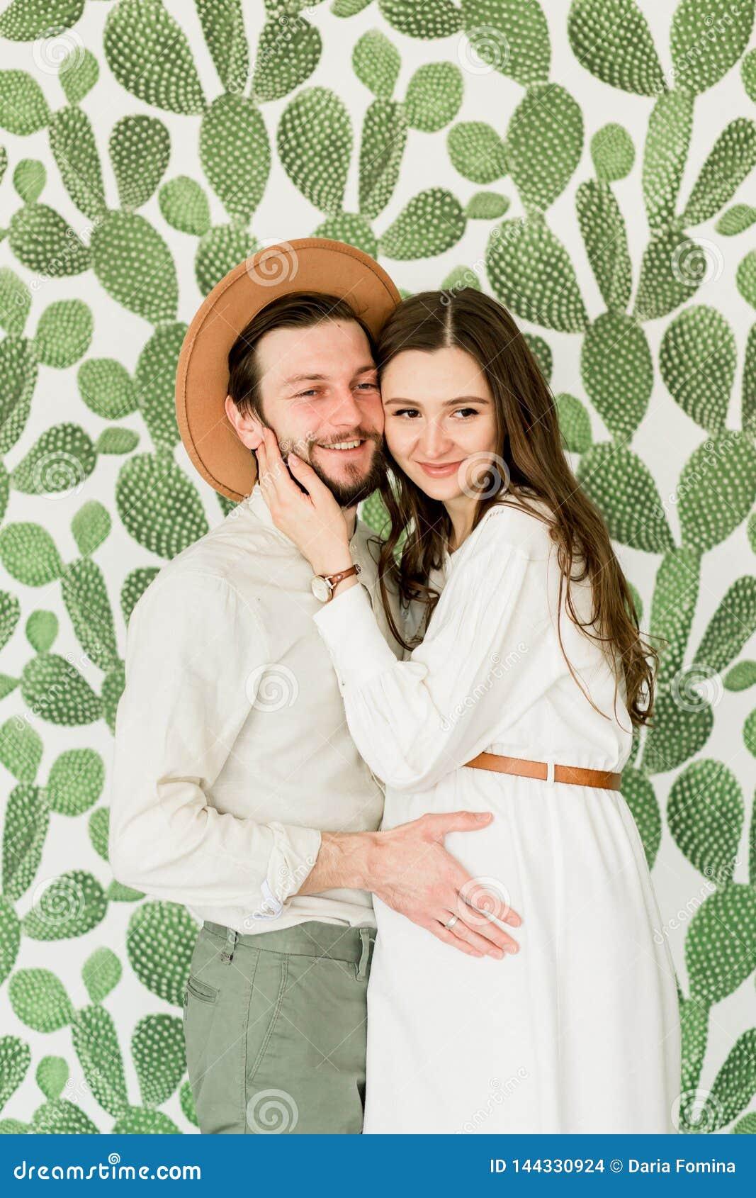 Νέα όμορφη έγκυος γυναίκα και ο σύζυγός της στο καπέλο που στέκεται κοντά στον τοίχο κάκτων