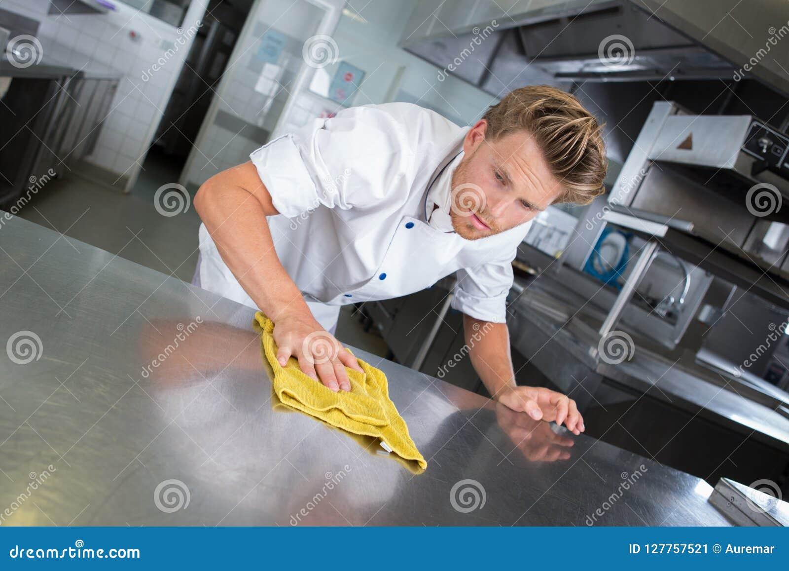 Νέα όμορφη αρσενική κουζίνα εστιατορίων μαγείρων καθαρίζοντας