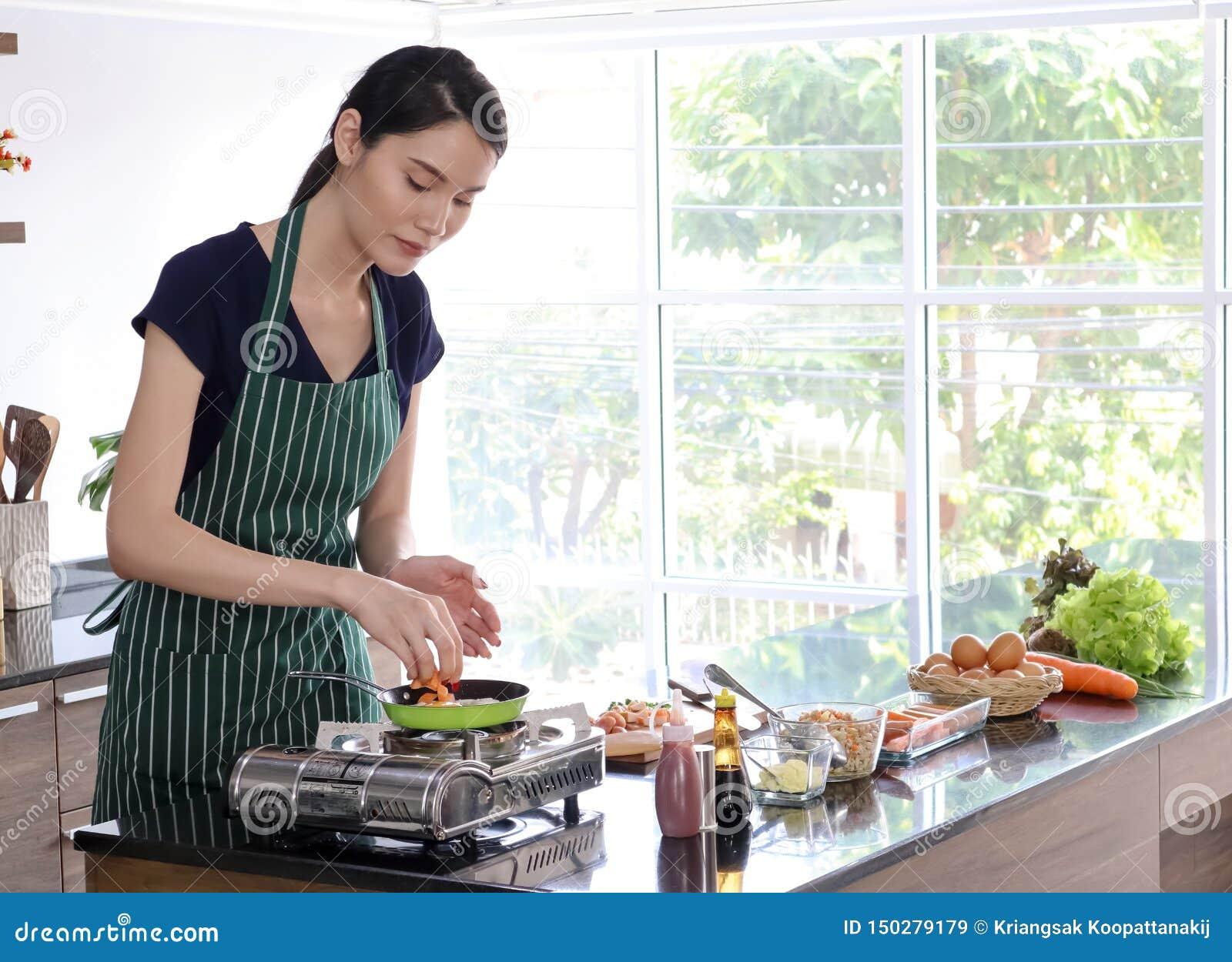 Νέα όμορφη ασιατική γυναίκα με τους πράσινους μάγειρες ποδιών λωρίδων στο τηγάνι