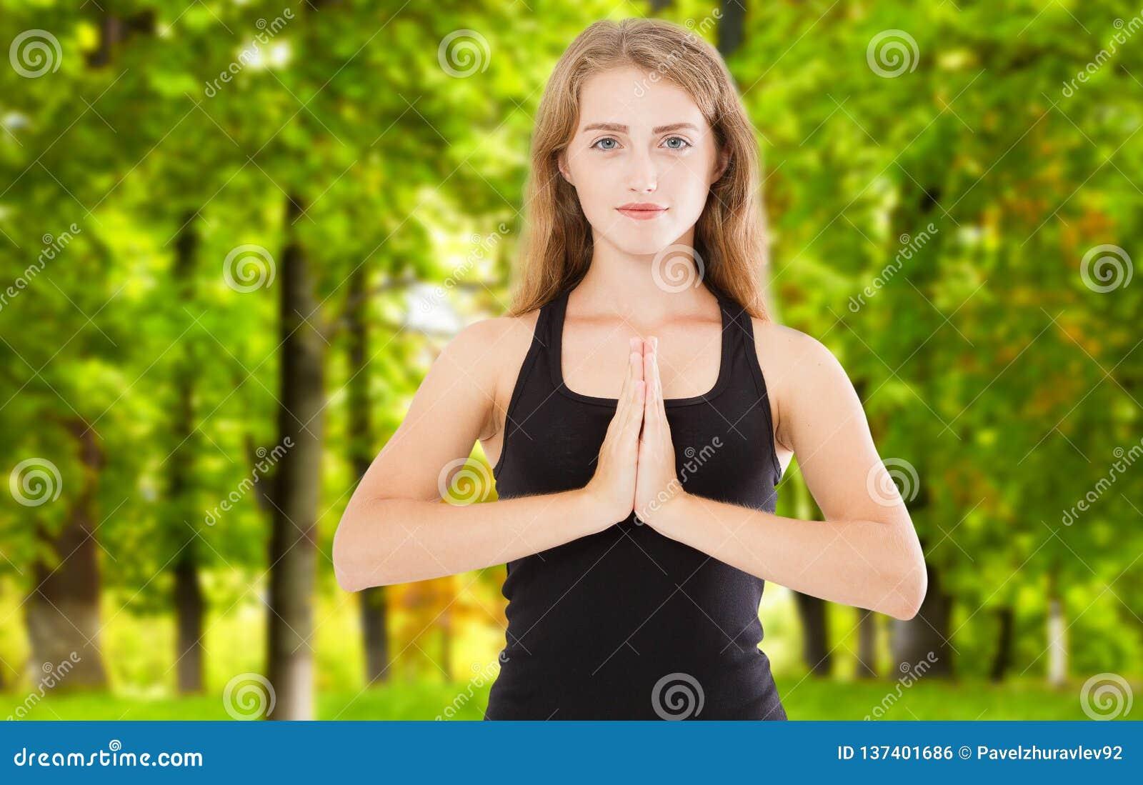 Νέα όμορφη γυναίκα με μακροχρόνιο σγουρό τρίχας στο ελαφρύ υπόβαθρο πάρκων Παραδίδει Namaste Προσεηθείτε, ευγνωμοσύνη, γιόγκα, Θε