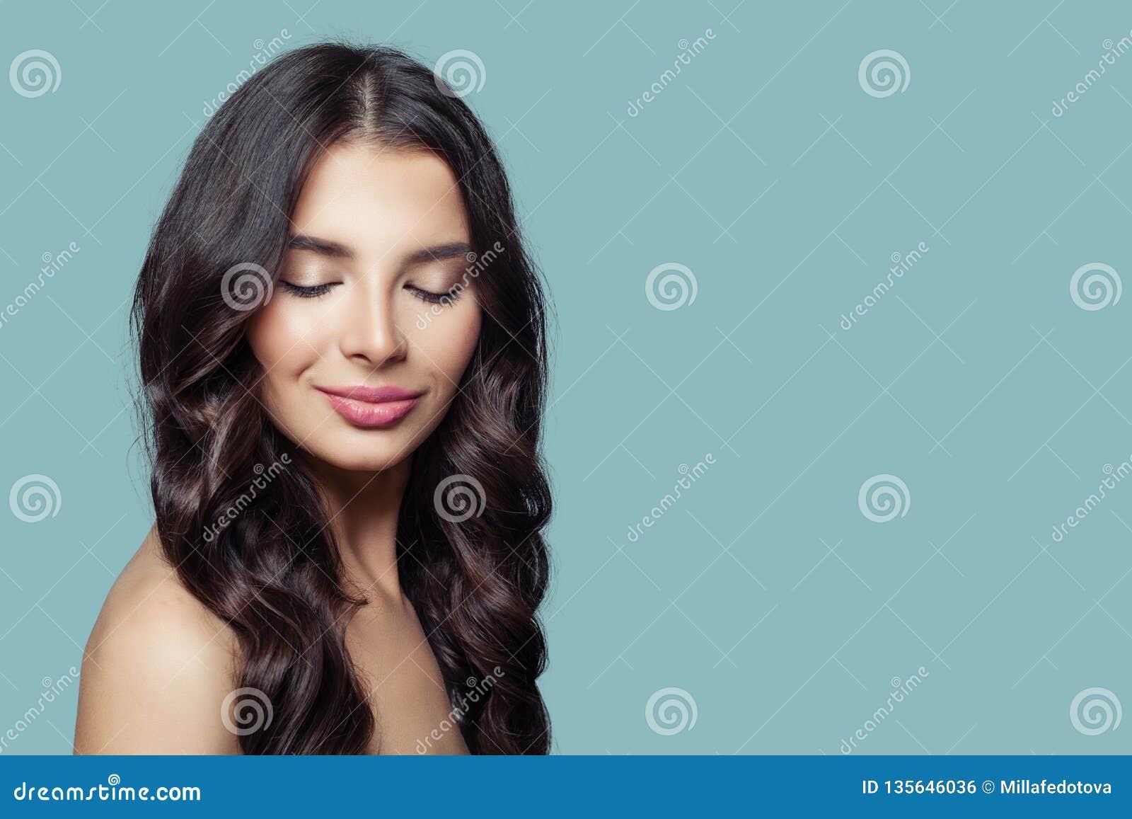 Νέα όμορφη γυναίκα με τη μακριά υγιή τρίχα και φυσικό makeup στο μπλε υπόβαθρο