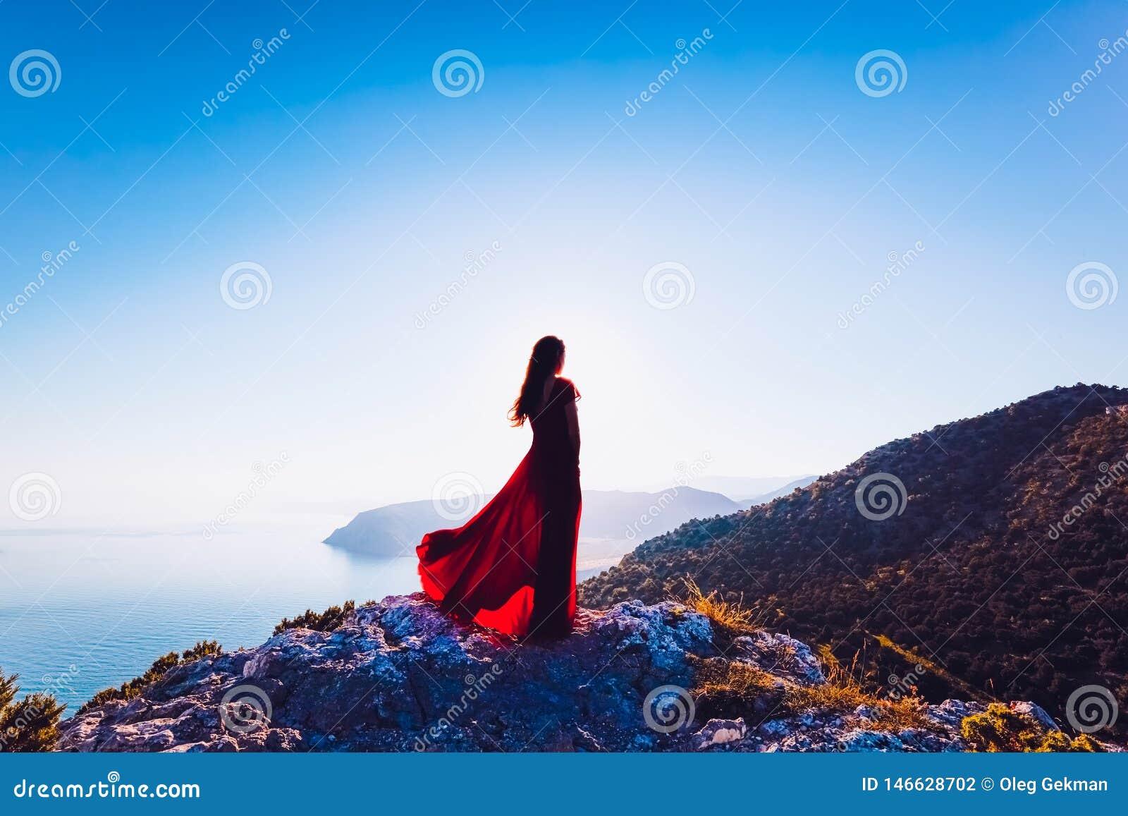 Νέα όμορφη γυναίκα στο κόκκινο φόρεμα που κοιτάζει στη θάλασσα βουνών