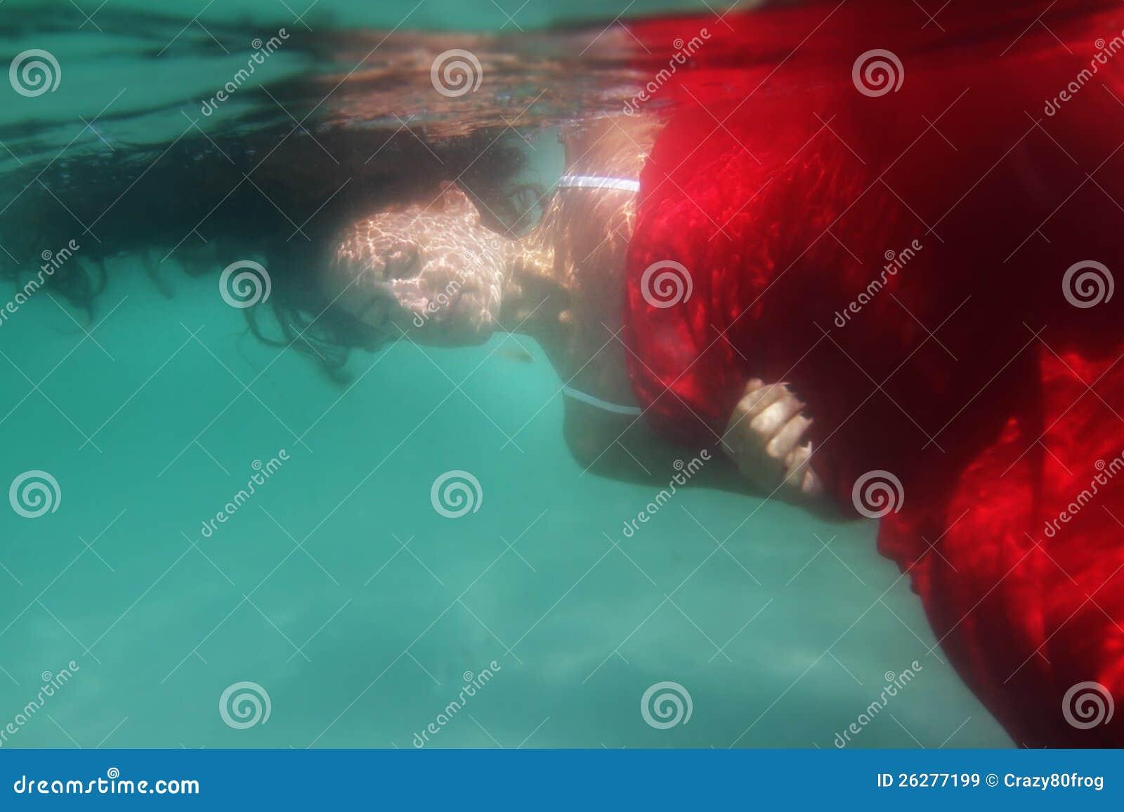 Νέα όμορφη γυναίκα στο κόκκινο φόρεμα υποβρύχιο