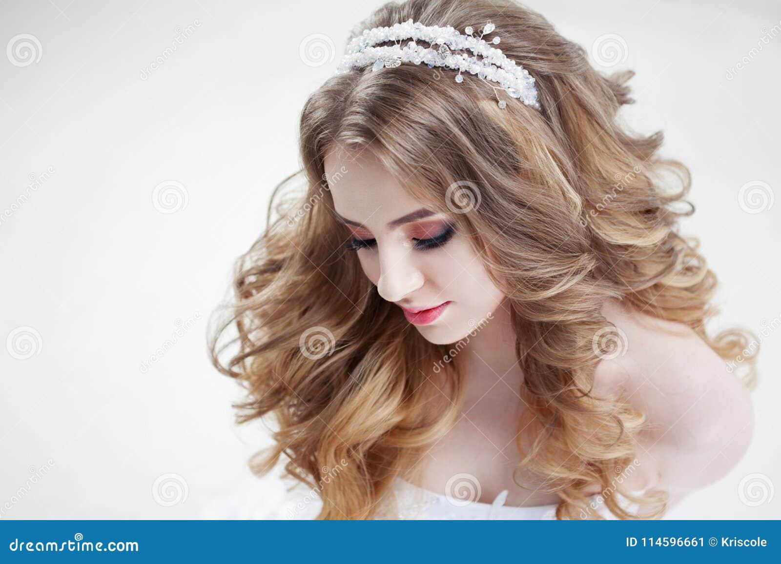 511ec57062 Νέα όμορφη νύφη με τις πολυτελείς μπούκλες Γάμος hairstyle με την τιάρα  Πορτρέτο κινηματογραφήσεων σε πρώτο πλάνο στο ελαφρύ υπόβαθρο. Φωτογραφία  ...