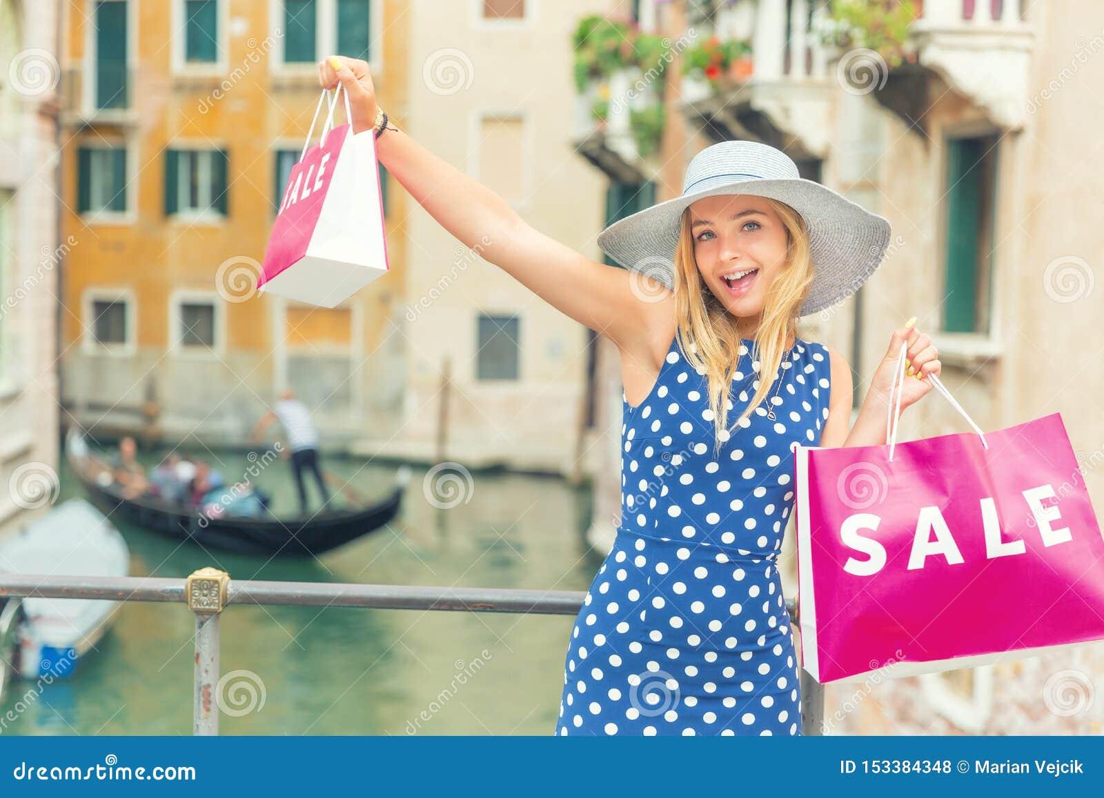 Νέα όμορφη ξανθή γυναίκα στο κέντρο της Βενετίας με τις τσάντες αγορών και την ευχαρίστηση της αγοράς Μόδας gir Ιταλία που διαστί