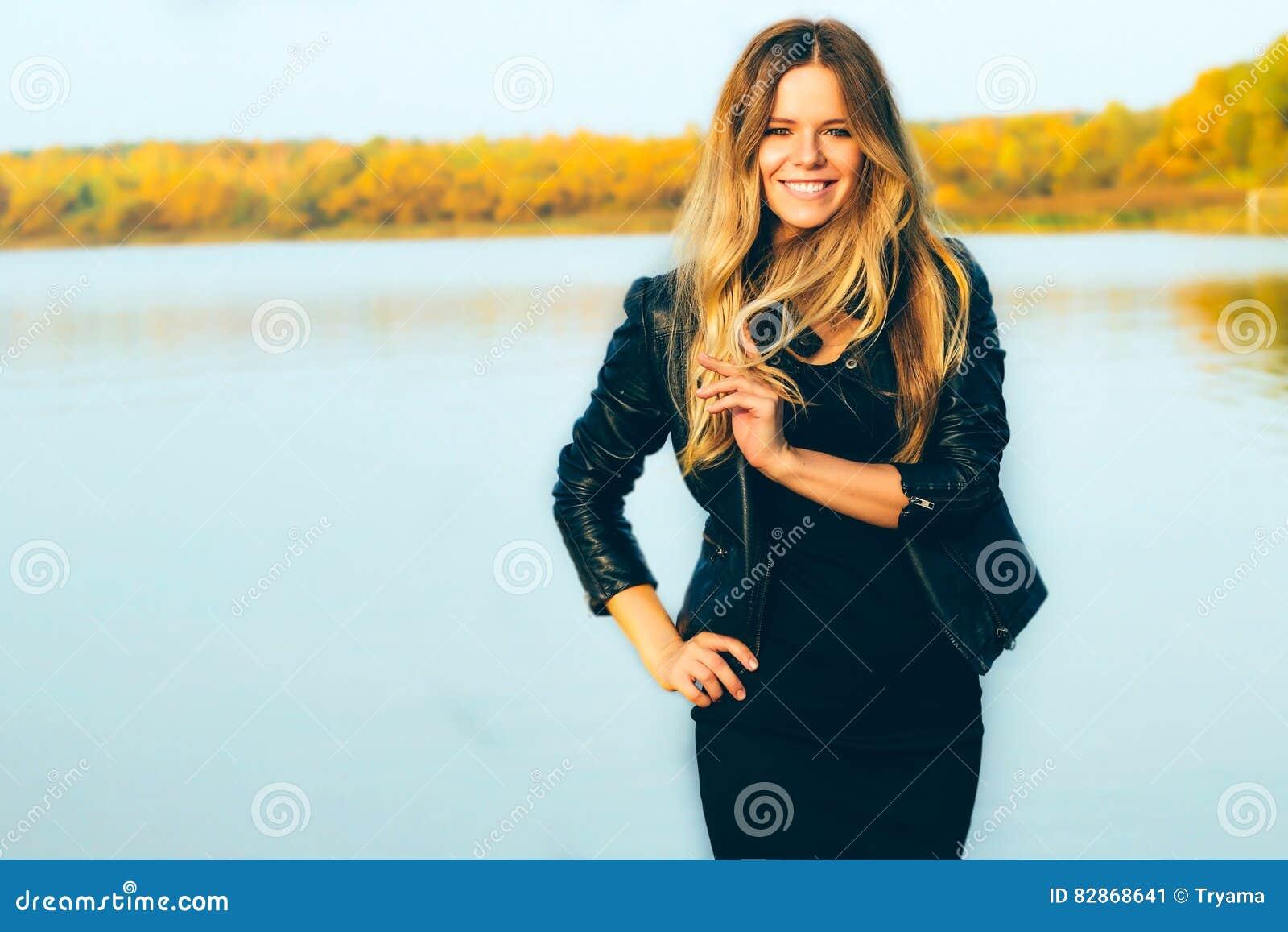 Νέα όμορφη ξανθή γυναίκα στο πάρκο φθινοπώρου με τη λίμνη στα σκοτεινά τέλεια δόντια χαμόγελου σακακιών δέρματος κατά τη διάρκεια
