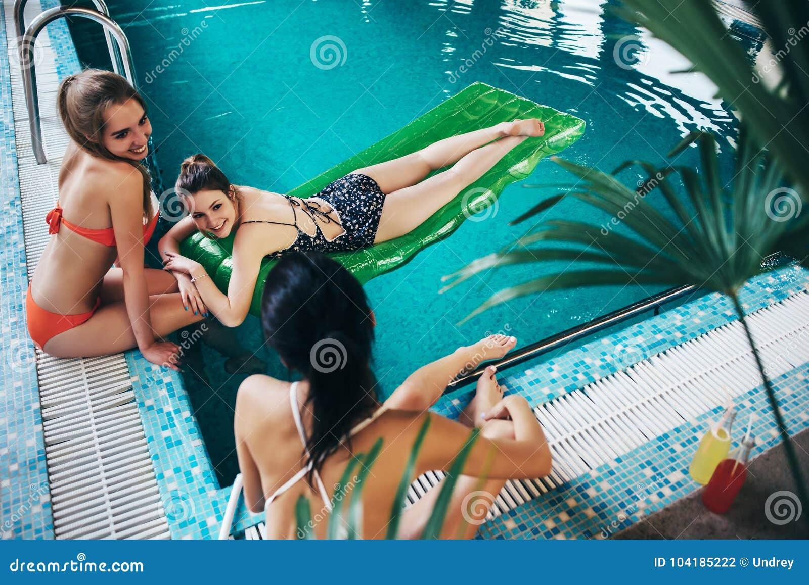 Νέες φίλες που φορούν τη swimwear χαλάρωση swimming-pool που μιλά και που χαμογελά
