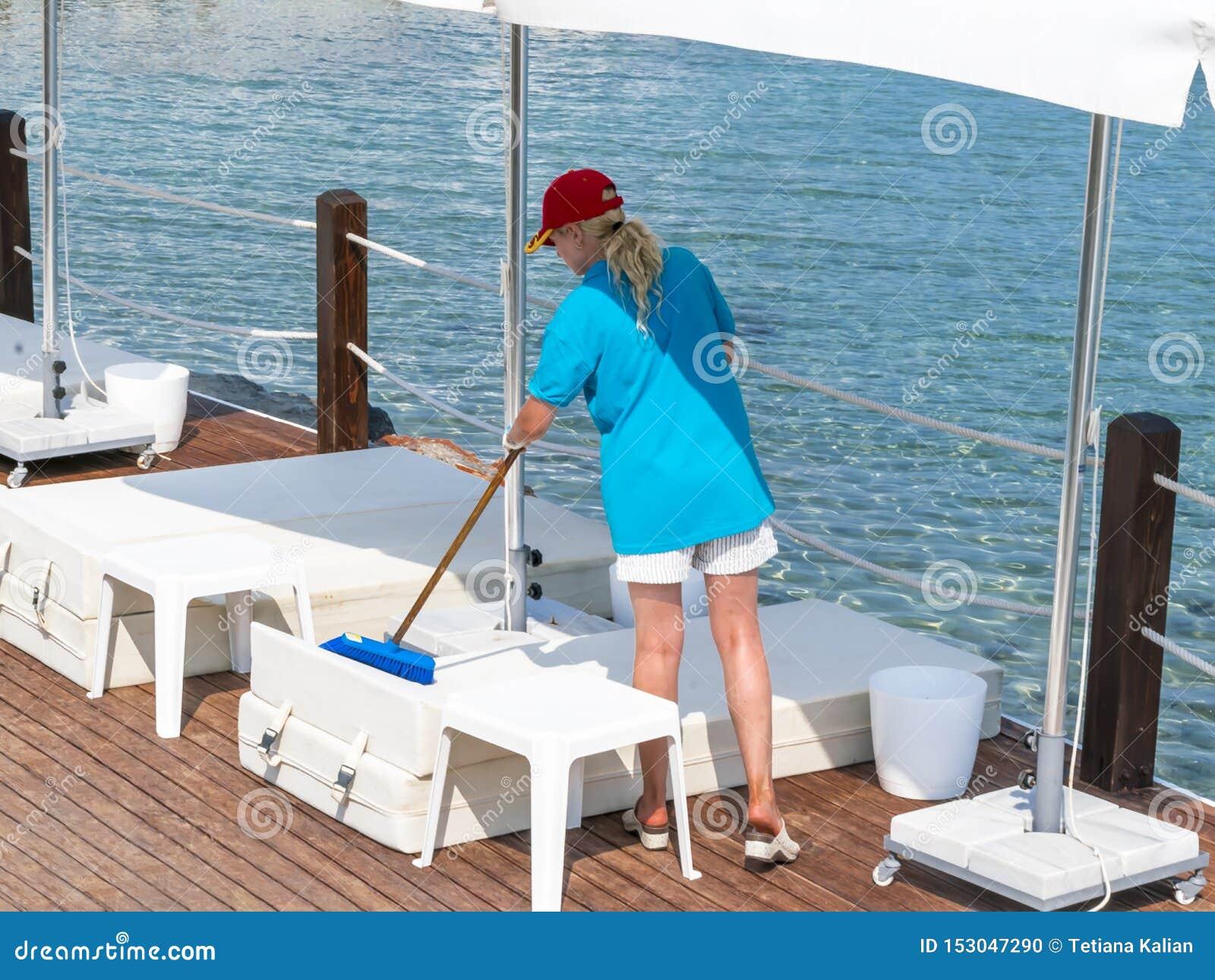 Νέοι θηλυκοί καθαρίζοντας αργόσχολοι θερινών παραλιών Πρόσωπο που εργάζεται χρησιμοποιώντας τα εργαλεία
