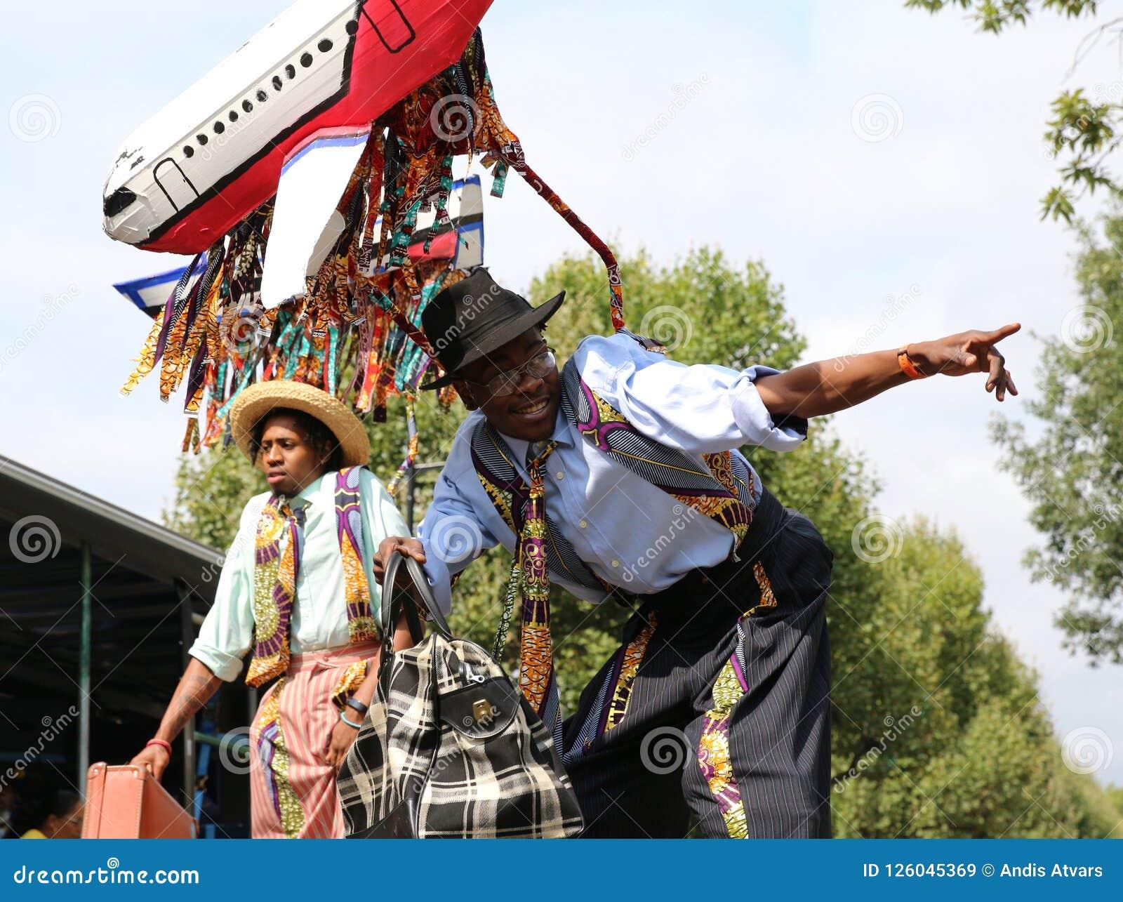 Νέοι καλλιτέχνες καρναβαλιού Νότινγκ Χιλ στα ξυλοπόδαρα που θέτουν ενάντια στο μπλε ουρανό
