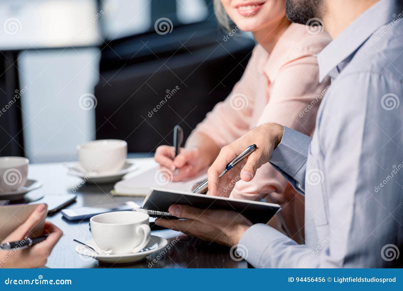 Νέοι που πίνουν τον καφέ και που γράφουν στα σημειωματάρια στην επιχειρησιακή συνεδρίαση, έννοια επιχειρησιακού μεσημεριανού γεύμ