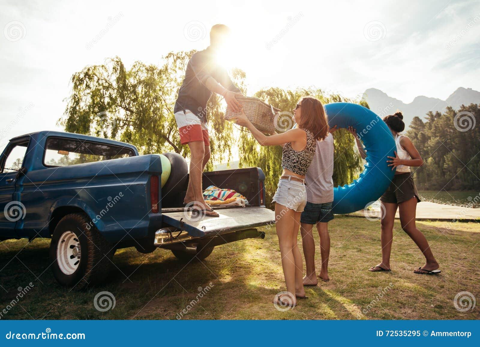 Νέοι φίλοι που ξεφορτώνουν το ανοιχτό φορτηγό στο ταξίδι στρατοπέδευσης
