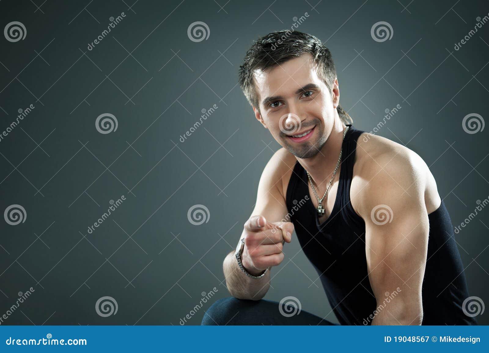 Νέος αθλητικός τύπος σε ένα κοστούμι που δείχνει με το δάχτυλό του