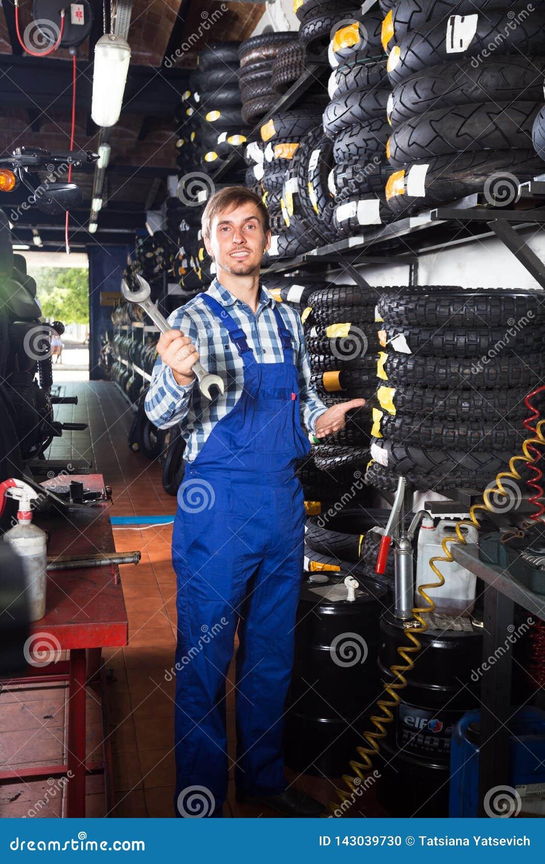 Νέος αρσενικός μηχανικός που εργάζεται στο αυτόματο κατάστημα επισκευής
