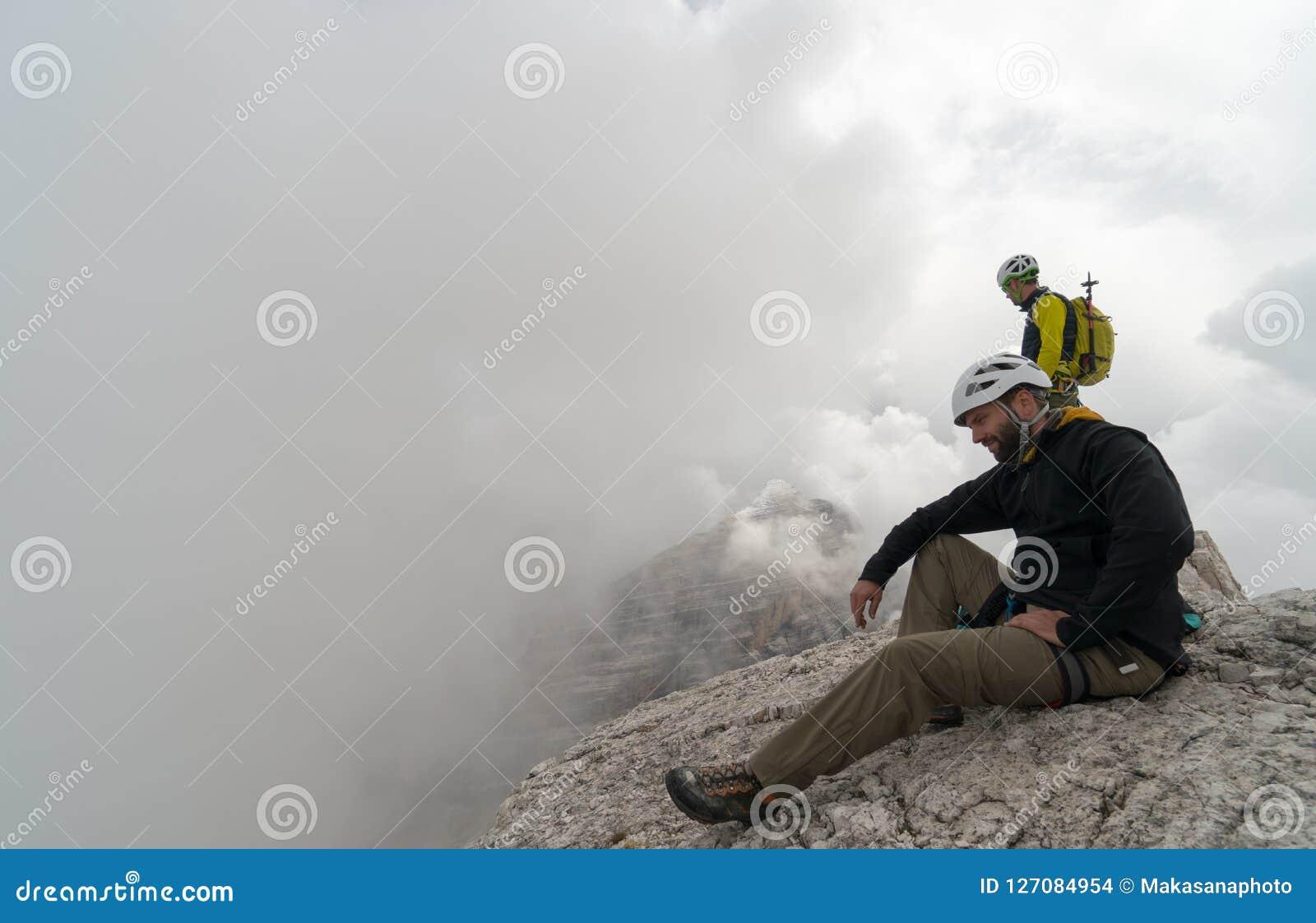 Νέος αρσενικός ορειβάτης βουνών σε μια αιχμή βουνών δολομίτη που απολαμβάνει τη θέα με τον οδηγό του που στέκεται πίσω