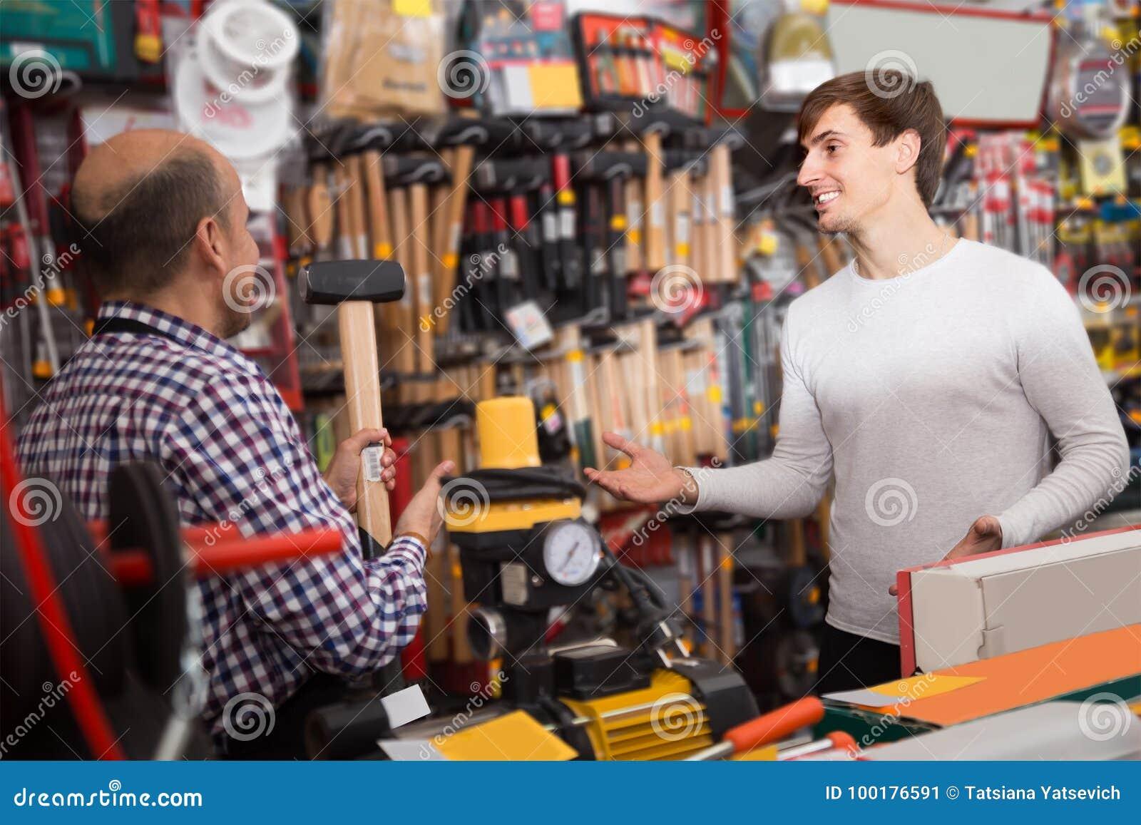 Νέος αρσενικός πελάτης και ώριμος πωλητής στη σχεδίαση του τμήματος