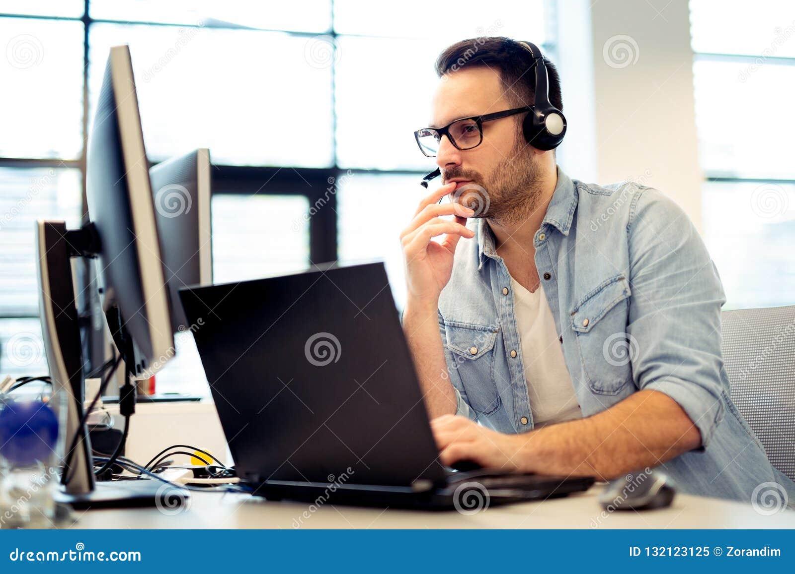 Νέος αρσενικός χειριστής τηλεφωνικών κέντρων που εργάζεται στον υπολογιστή του ενώ γεια