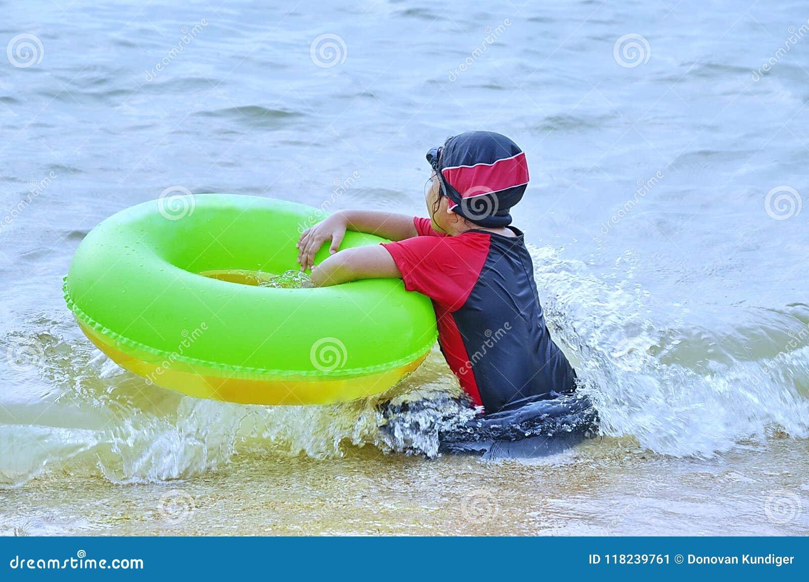 Νέος Ασιάτης κάθεται στην κυματωγή σε μια ωκεάνια παραλία με doughnut της