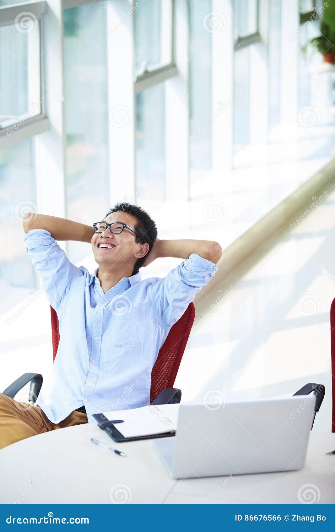Νέος ασιατικός επιχειρηματίας που εργάζεται στο γραφείο