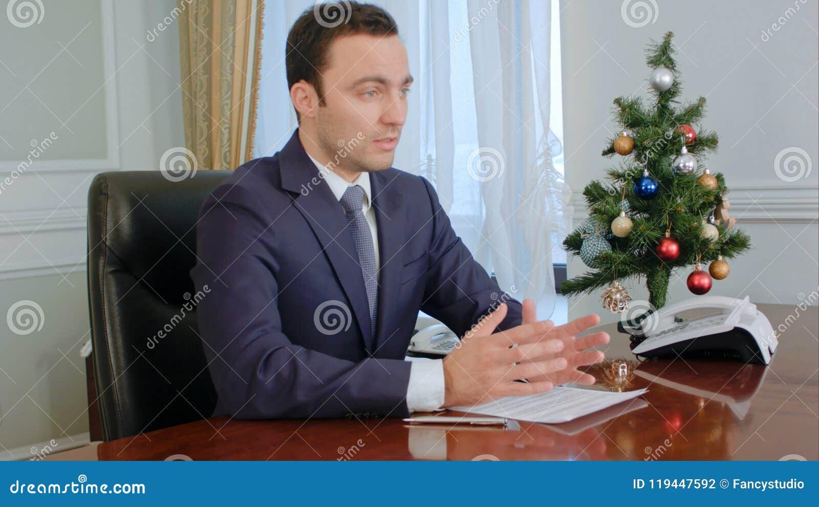 Νέος επιχειρηματίας που λέει τις καλές ειδήσεις καθμένος από τον πίνακα στην αρχή