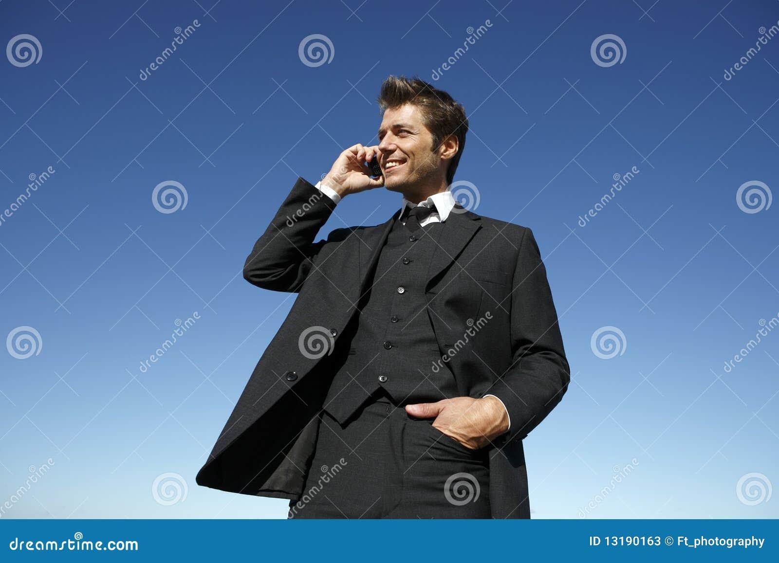 Νέος επιχειρηματίας στο κοστούμι στο τηλέφωνο υπαίθρια