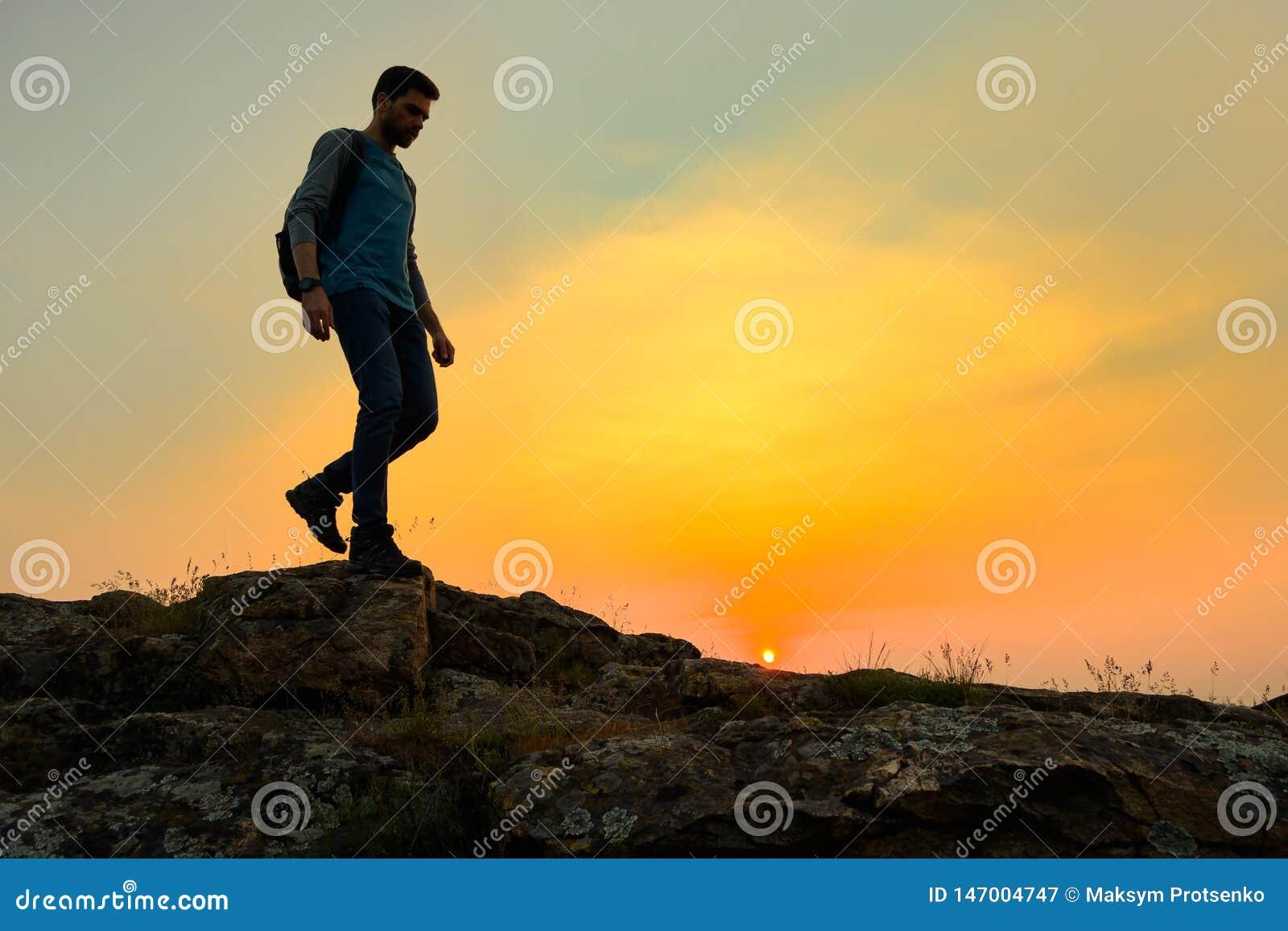Νέος ευτυχής ταξιδιώτης ατόμων που με το σακίδιο πλάτης στο δύσκολο ίχνος στο θερμό θερινό ηλιοβασίλεμα Έννοια ταξιδιού και περιπ