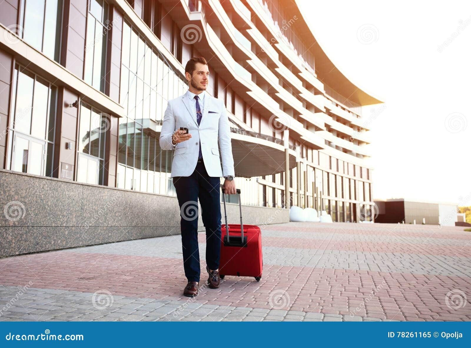 Νέος ευτυχής ταξιδιωτικός επιχειρηματίας που κάνει την κλήση μετά από να φθάσει στο ξενοδοχείο έξω με τις αποσκευές του