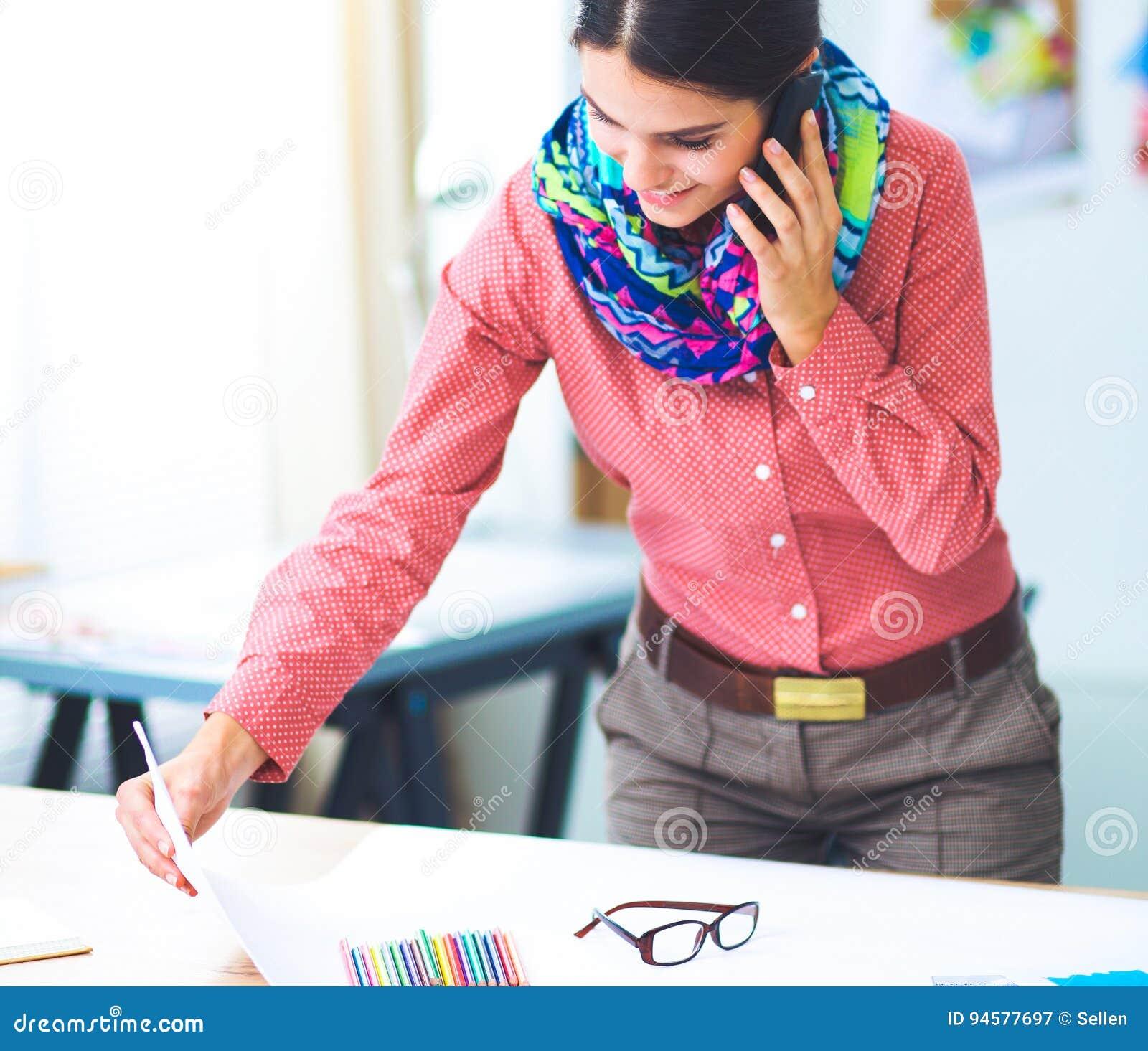 Νέος ελκυστικός θηλυκός σχεδιαστής μόδας που εργάζεται στο γραφείο γραφείων, που σύρει μιλώντας σε κινητό
