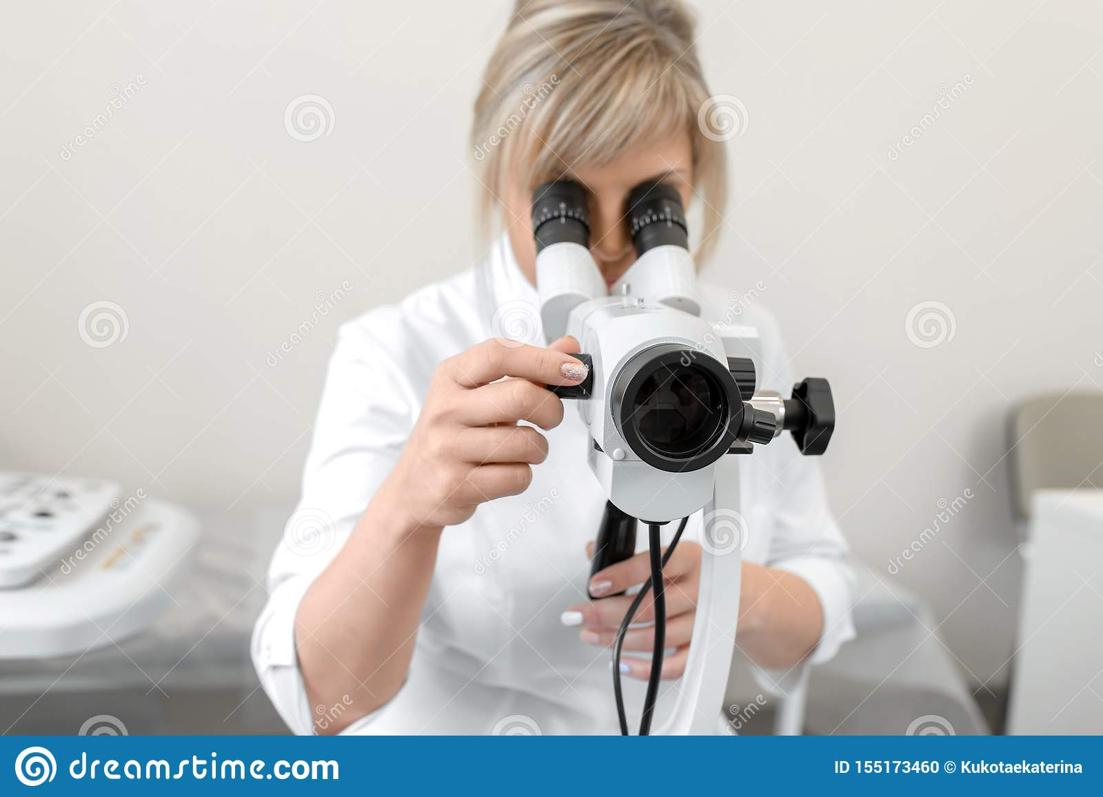 Νέος θηλυκός επαγγελματικός gynecologist στη διαδικασία εργασίας, εξετάζει το colposcope