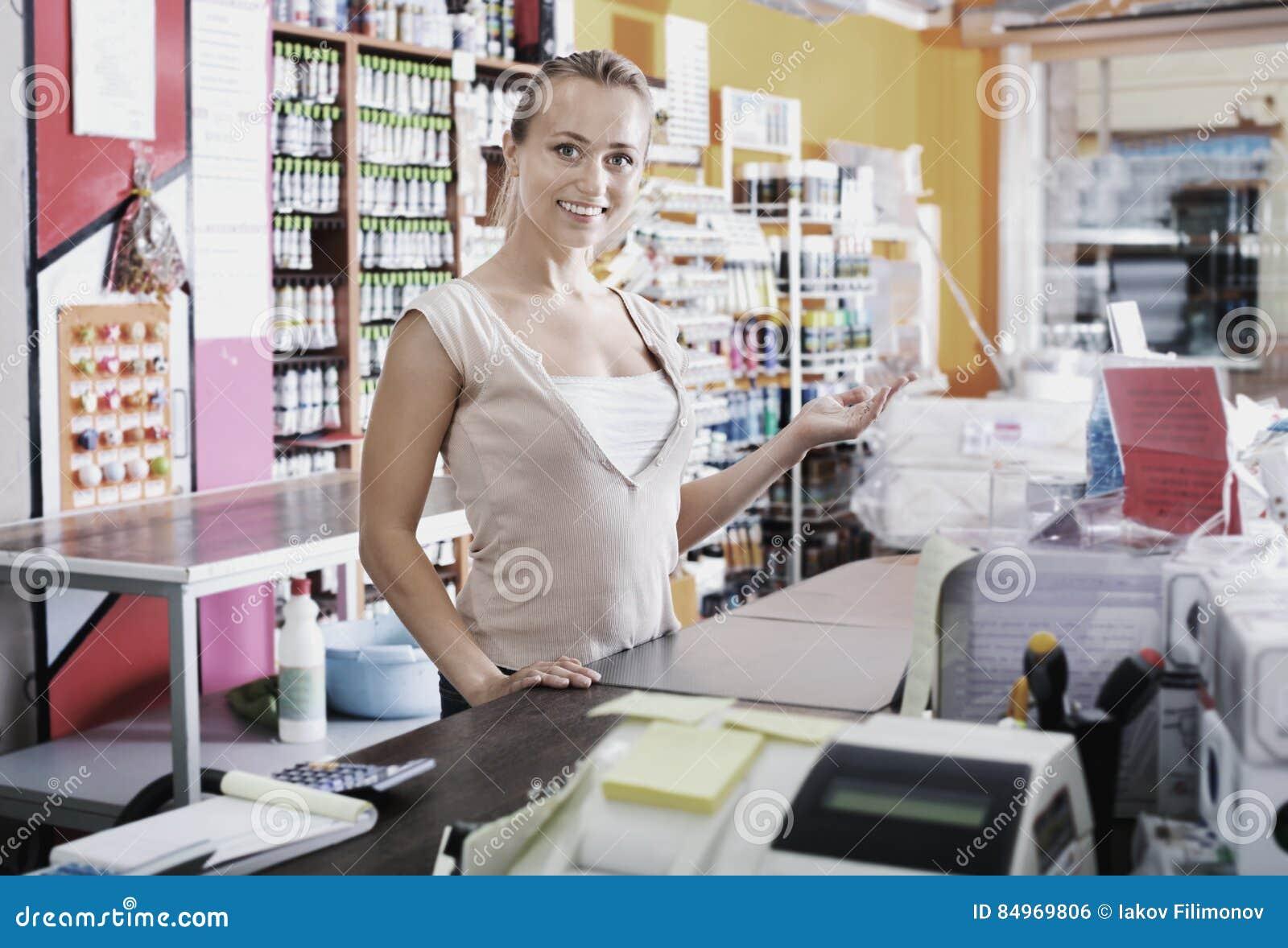 Νέος θηλυκός πωλητής που στέκεται στο γραφείο αμοιβής στην υπεραγορά