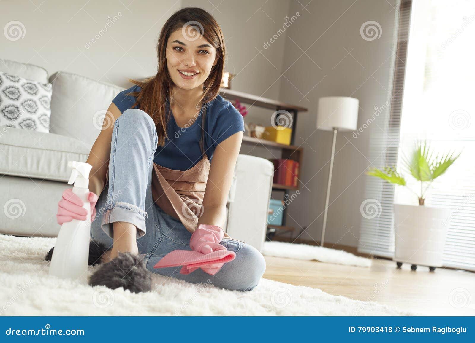 Νέος καθαρίζοντας τάπητας γυναικών στο δωμάτιο