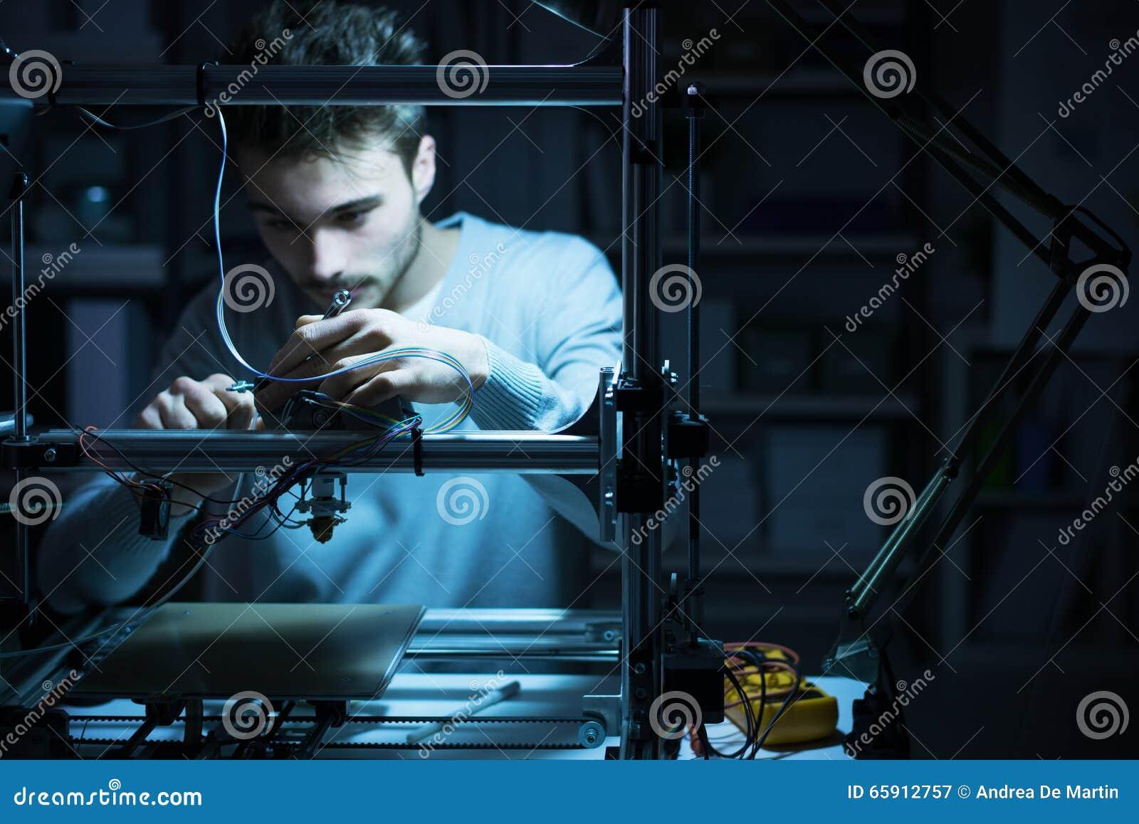 Νέος μηχανικός που εργάζεται σε έναν τρισδιάστατο εκτυπωτή