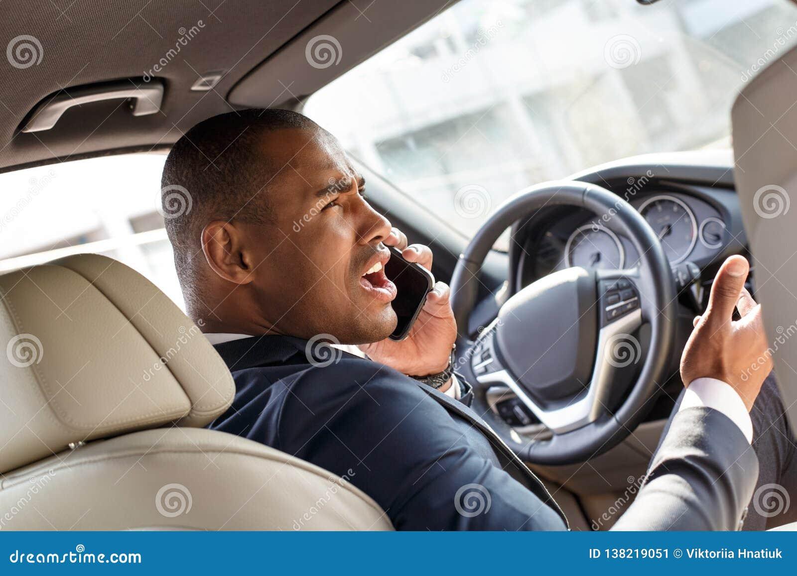 Νέος οδηγός επιχειρηματιών που οδηγεί το αυτοκίνητο που απαντάη στο τηλεφώνημα άποψη πίσω θέσεων