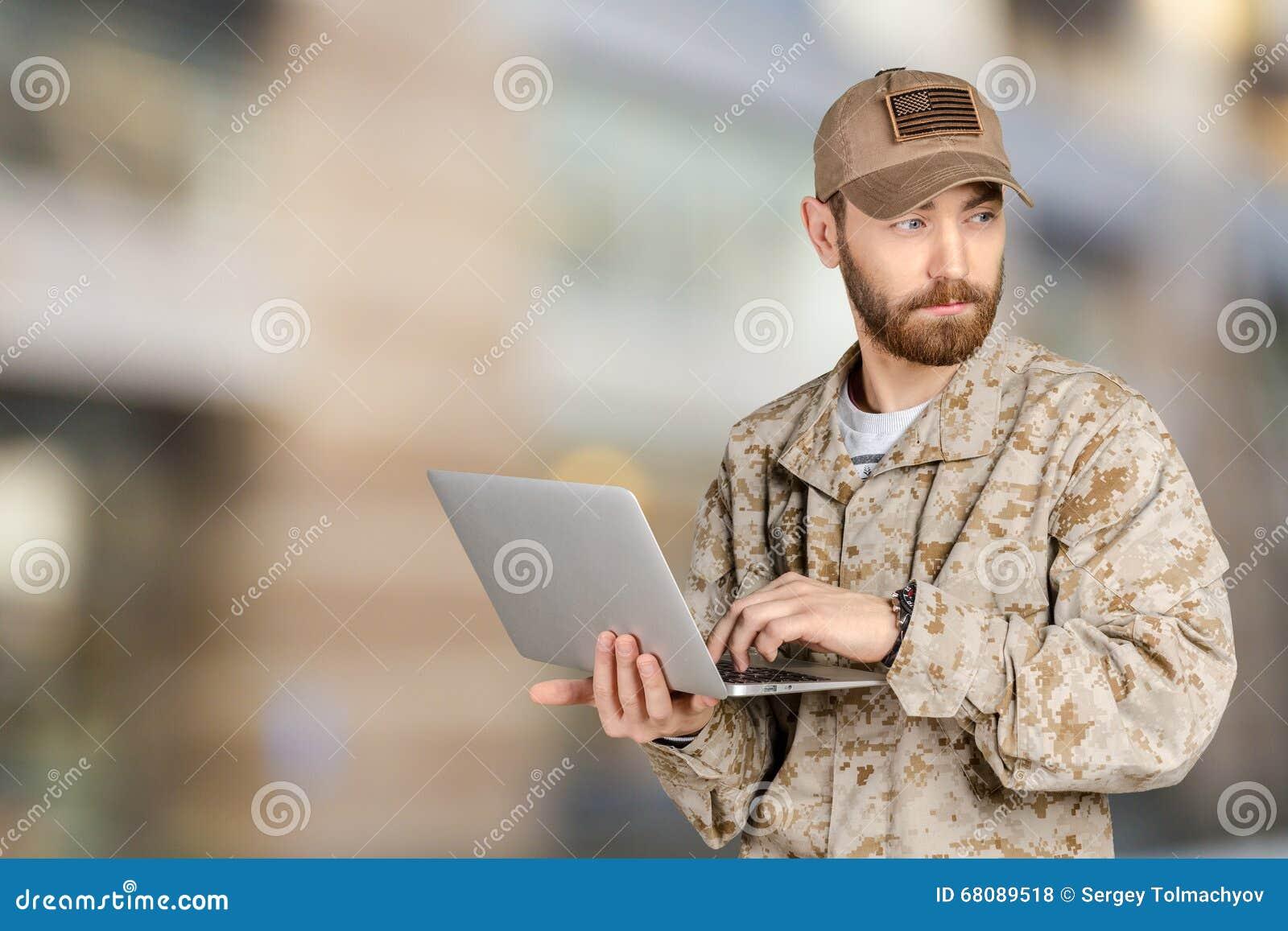 Νέος στρατιώτης στρατού με ένα lap-top