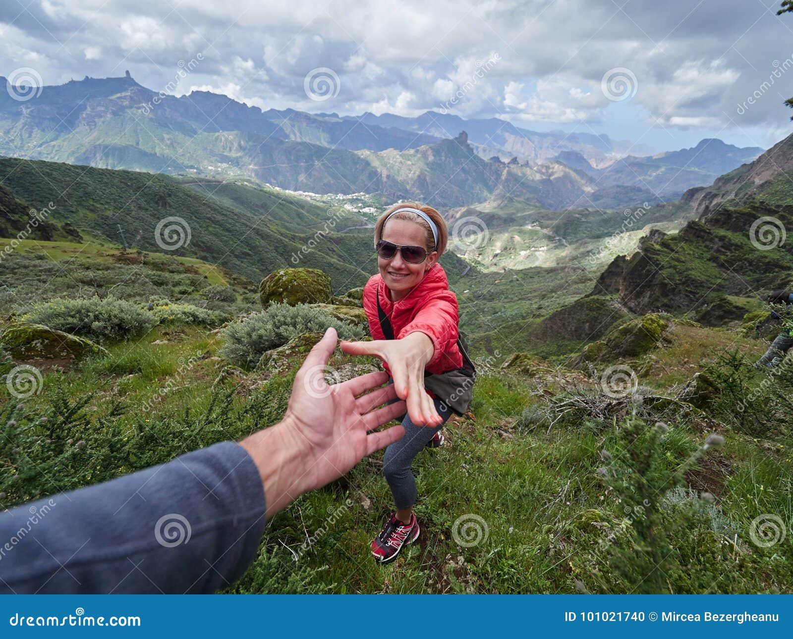 Νέος τουρίστας γυναικών στην αλπική ζώνη το καλοκαίρι, άνδρας που βοηθά την