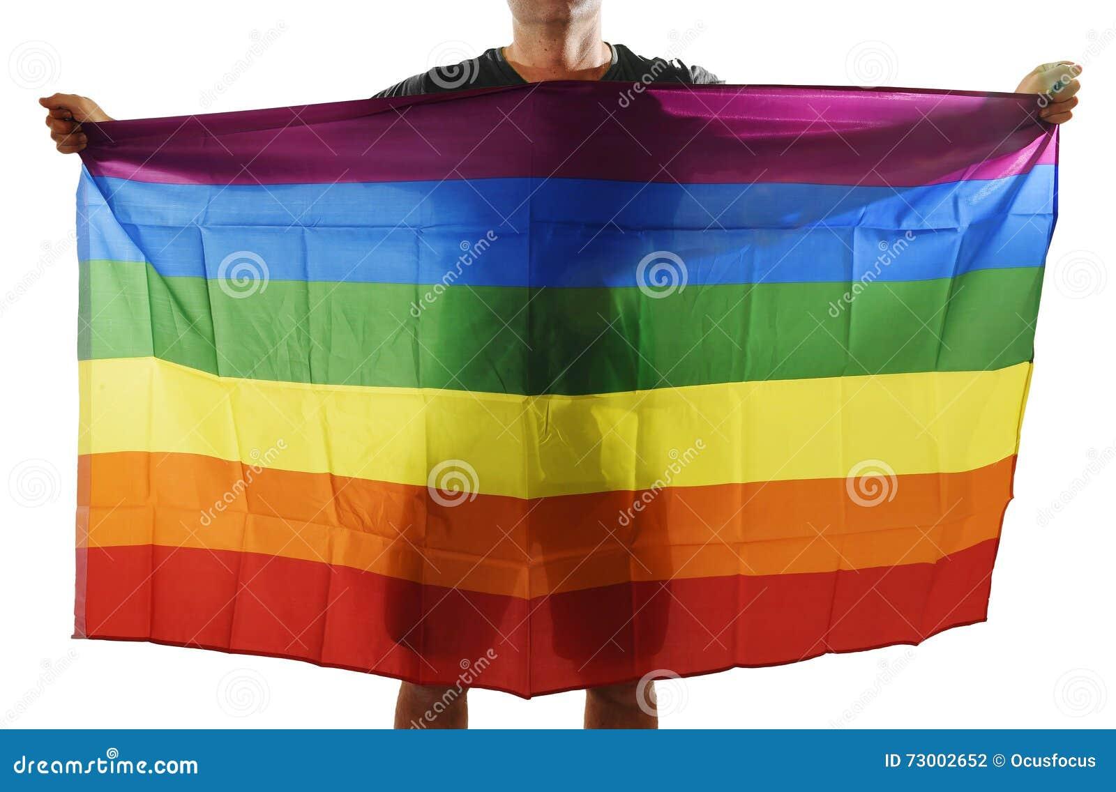 Νέος υπερήφανος ομοφυλόφιλος που διαδίδει την ευρεία μεγάλη ομοφυλοφιλική σημαία υπερηφάνειας με τη σκιά του πίσω από το ύφασμα