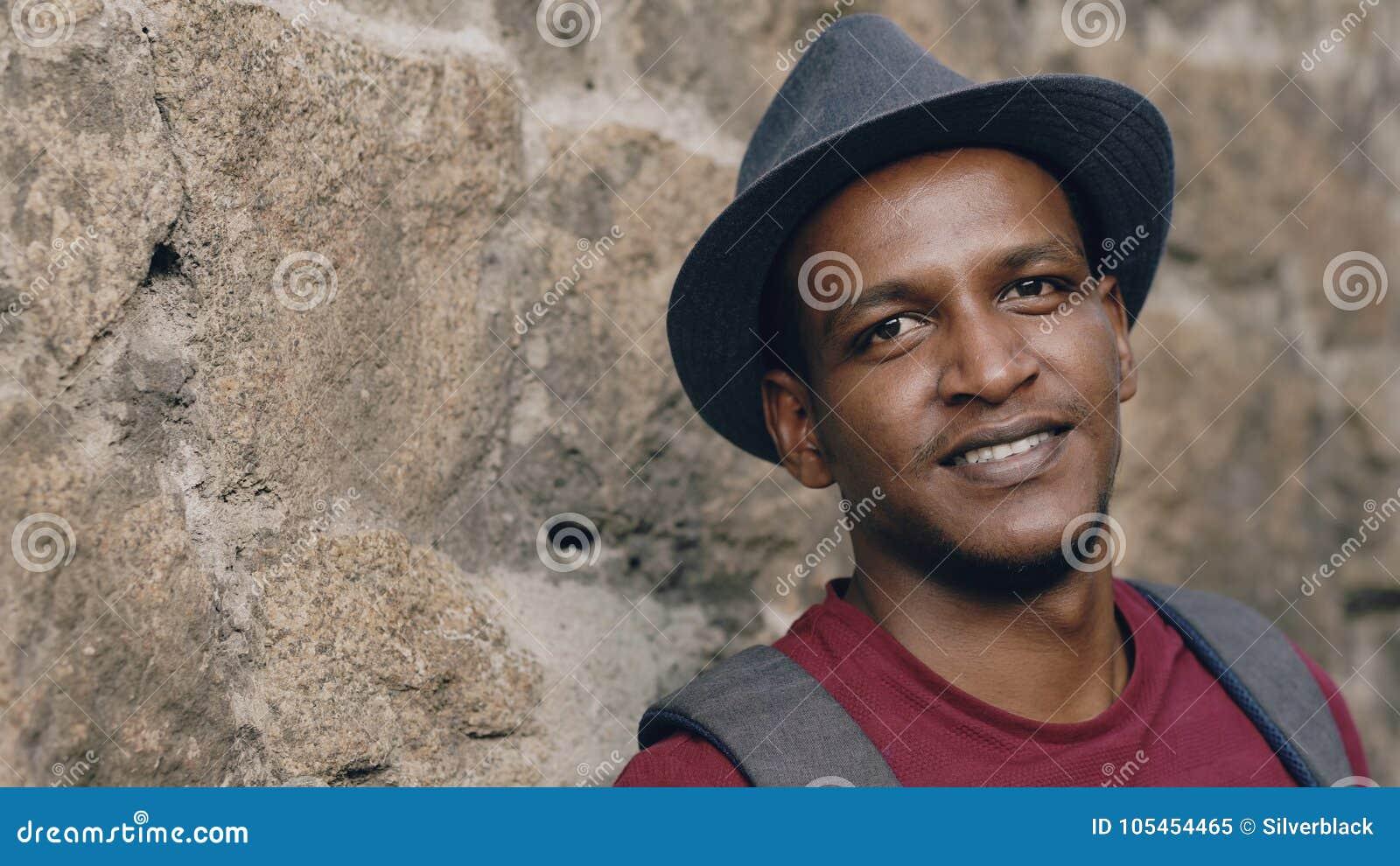 Νέος χαμογελώντας σπουδαστής univercity που χαμογελά και που εξετάζει τη κάμερα