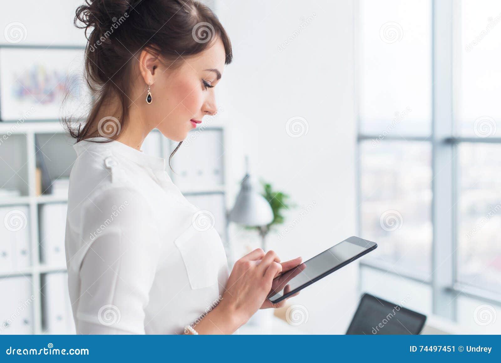 Νέος χαμογελώντας εργαζόμενος γραφείων θηλυκών στην ανάγνωση εργασιακών χώρων της, μηνύματα αγγελιών ειδήσεων ξεφυλλίσματος που χ