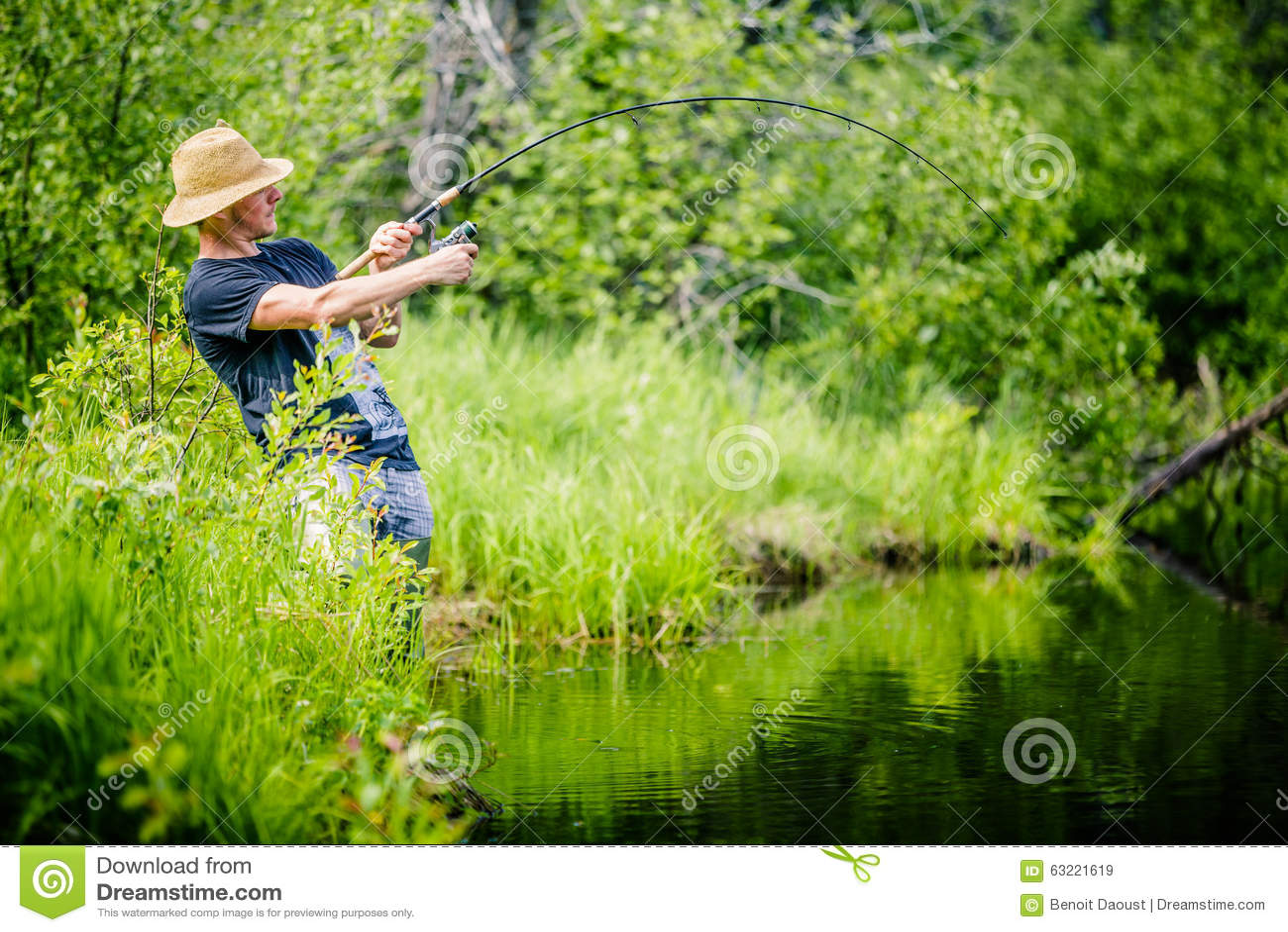 Νέος ψαράς που πιάνει ένα μεγάλο ψάρι