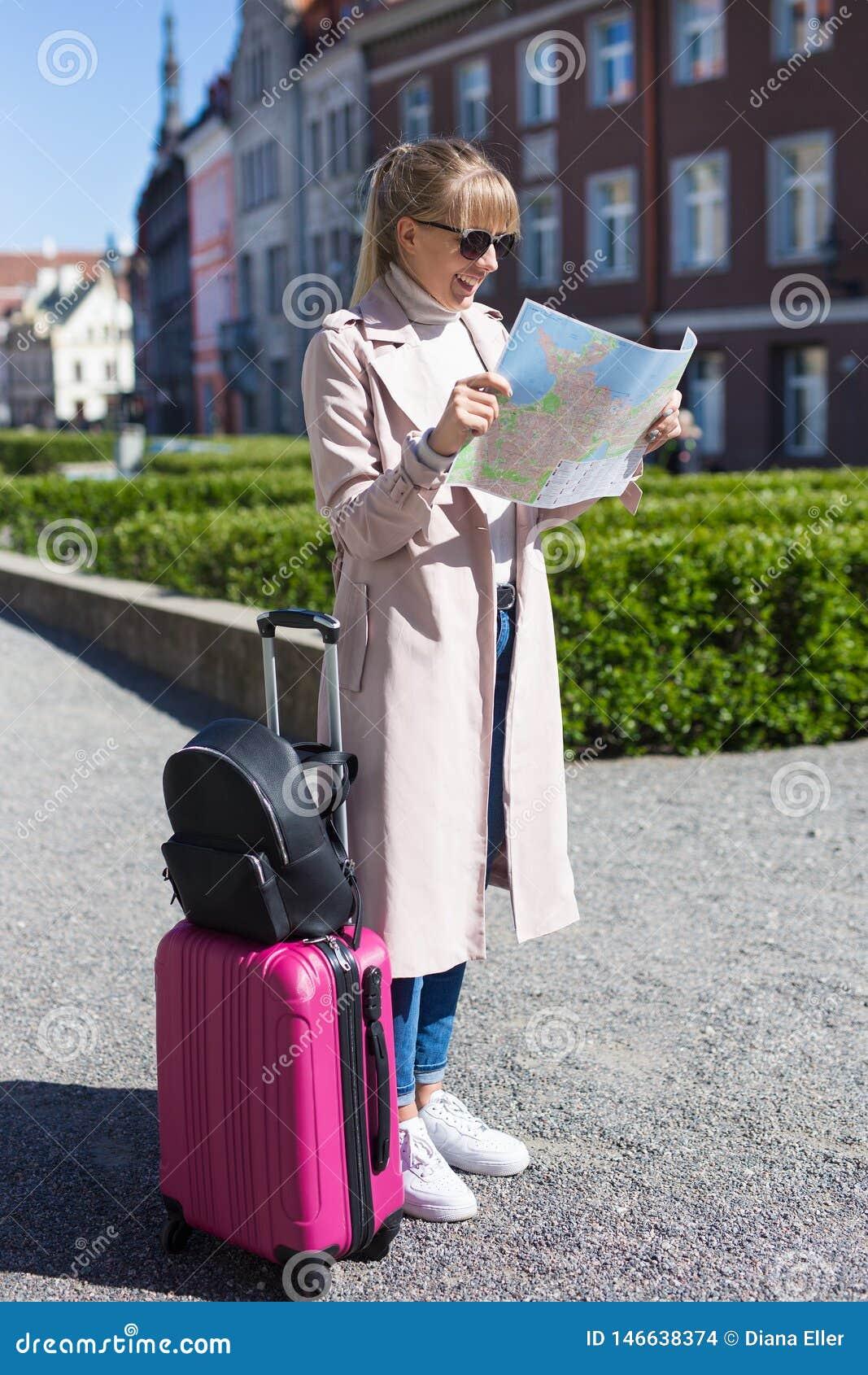 Νέος όμορφος θηλυκός ταξιδιώτης με τη βαλίτσα που χάνεται στην πόλη