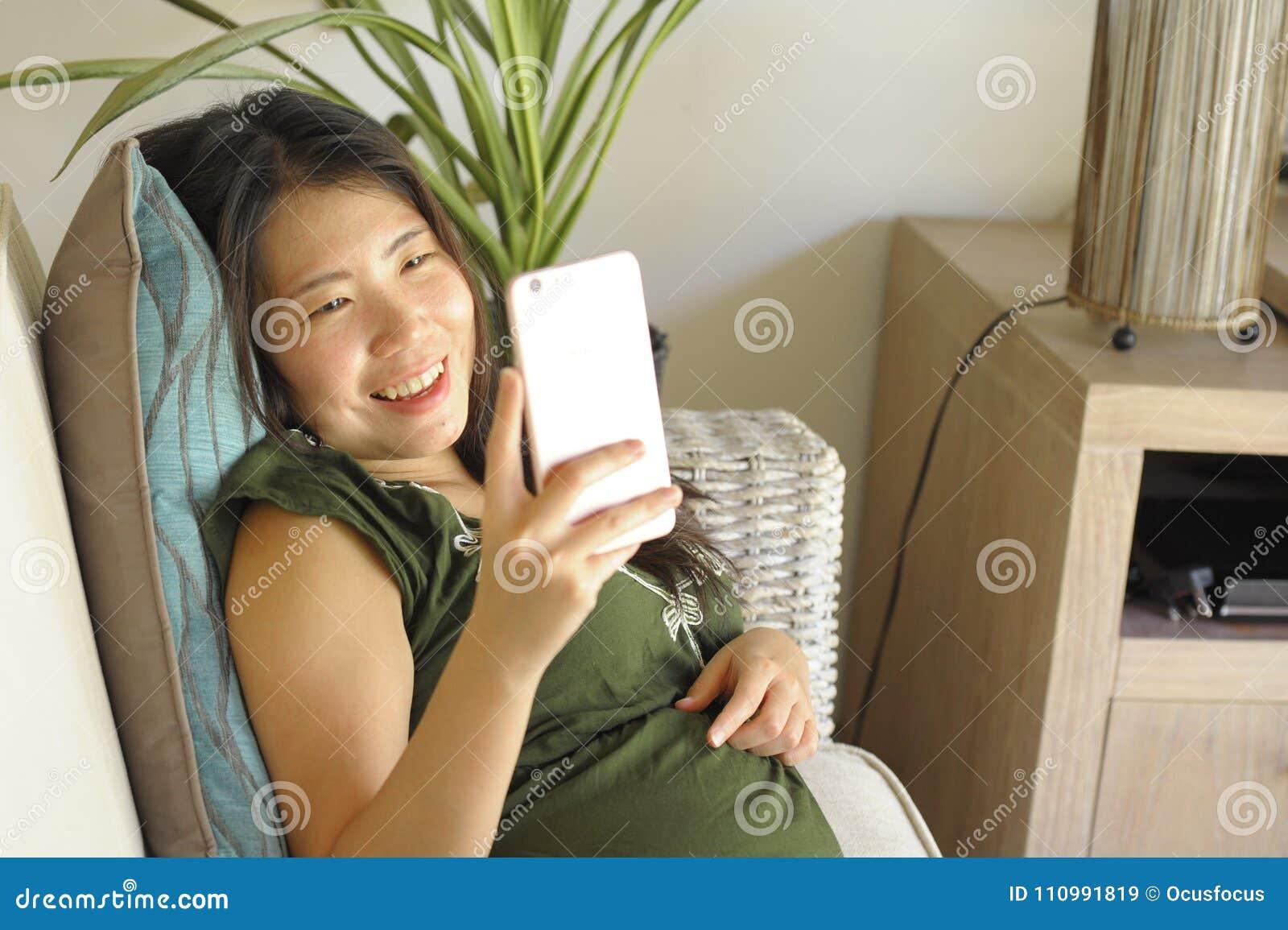 Νέος όμορφος και χαλαρωμένος ασιατικός κινεζικός καναπές καναπέδων καθιστικών γυναικών στο σπίτι που χρησιμοποιεί Διαδίκτυο στο κ