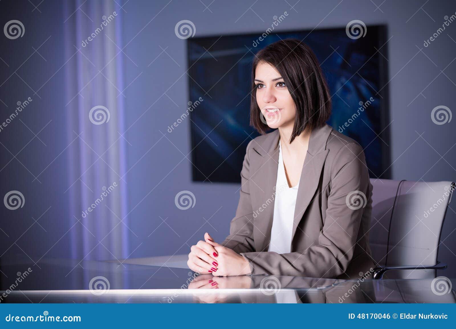 Νέος όμορφος τηλεοπτικός αναγγέλλων brunette στο στούντιο κατά τη διάρκεια της ζωντανής ραδιοφωνικής αναμετάδοσης Θηλυκός διευθυν