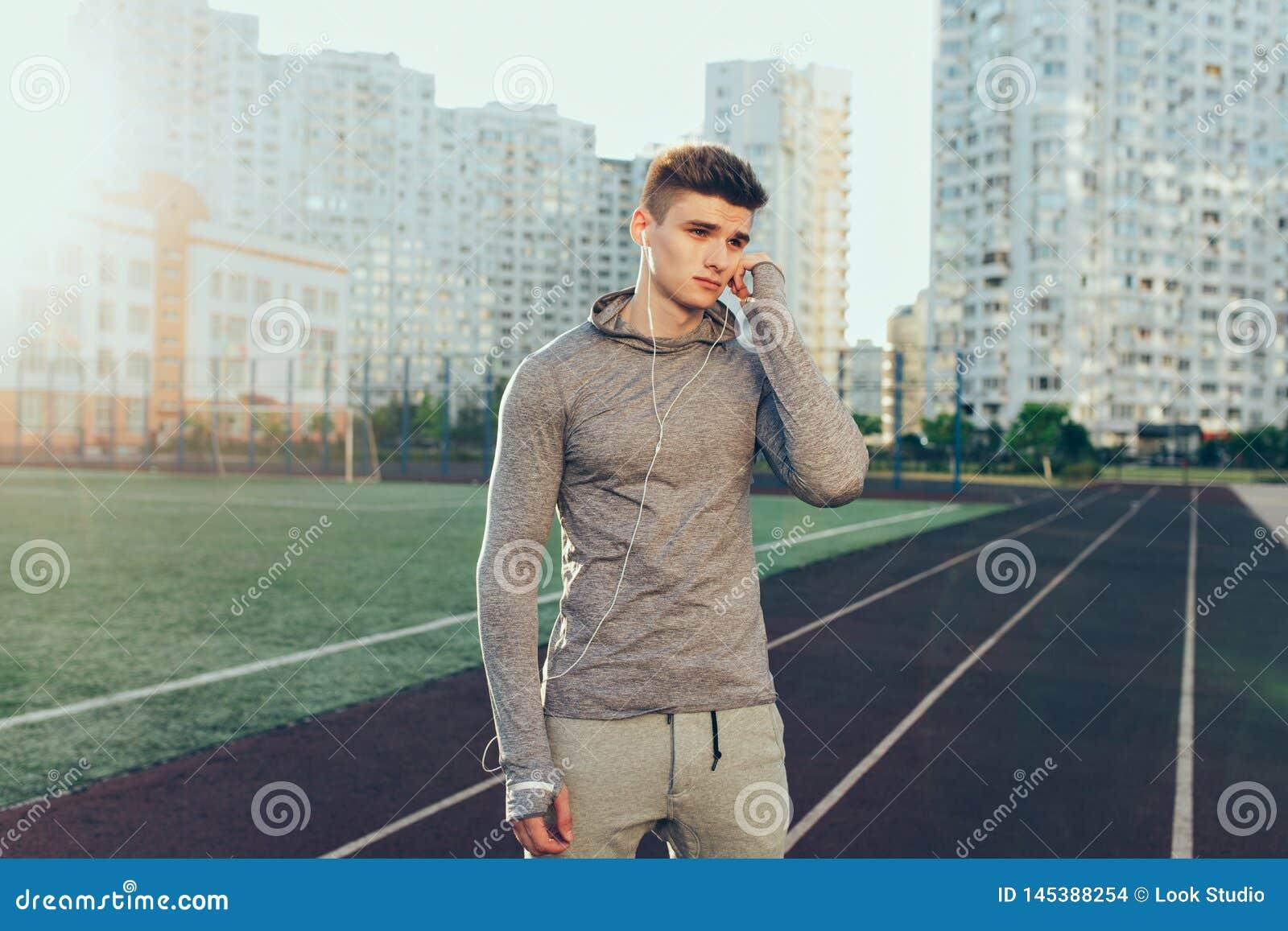 Νέος όμορφος τύπος στο γκρίζο αθλητικό κοστούμι στο τρέξιμο της διαδρομής στο υπόβαθρο κτηρίων στο πρωί Φορά το γκρίζο αθλητικό κ
