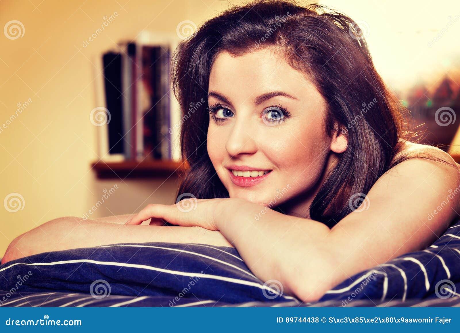 Νέος ύπνος γυναικών στα άσπρα κλινοσκεπάσματα στο κρεβάτι