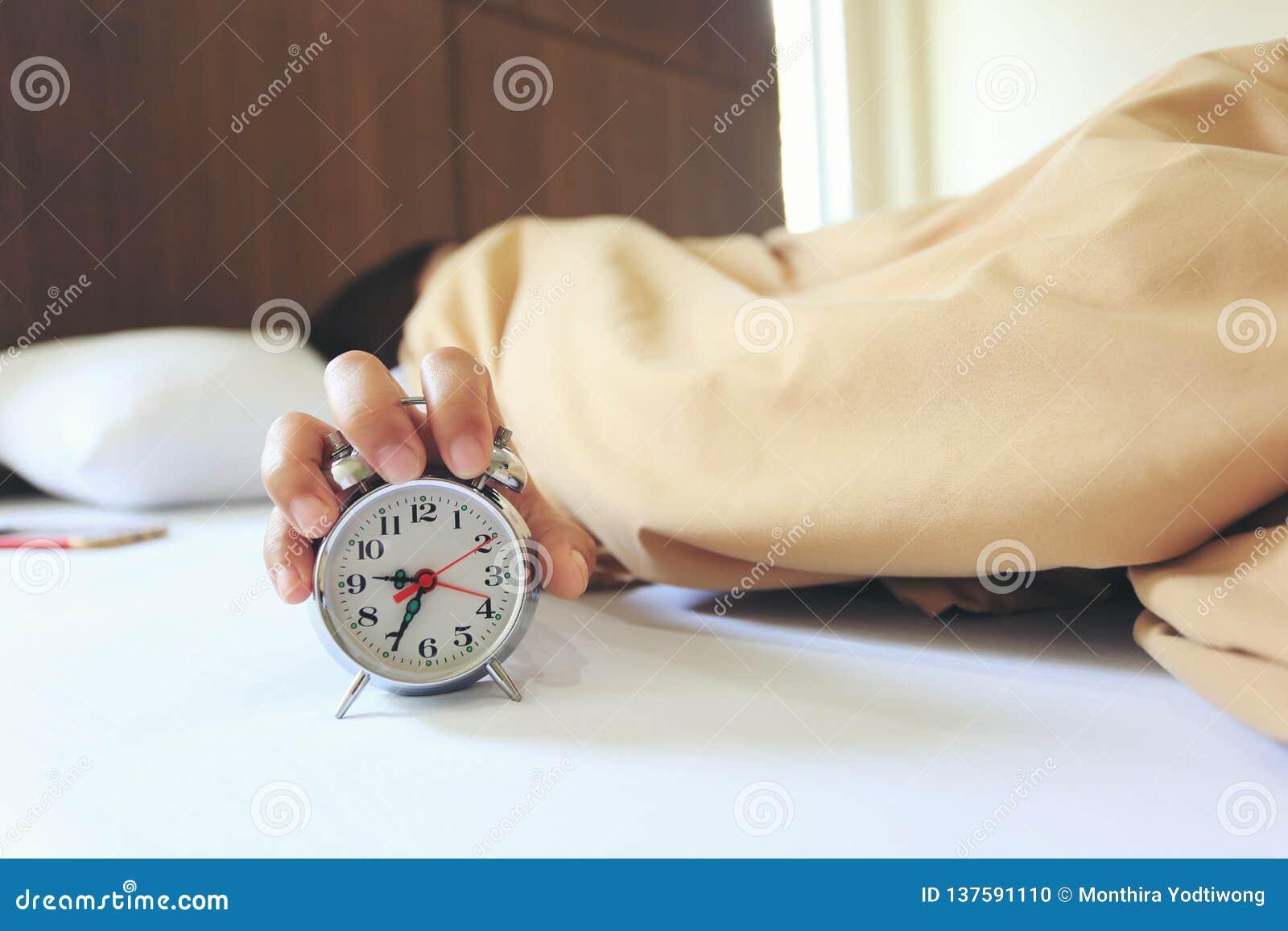 Νέος ύπνος γυναικών στην κρεβατοκάμαρα με τη λαβή το ξυπνητήρι το πρωί, έννοια υγείας